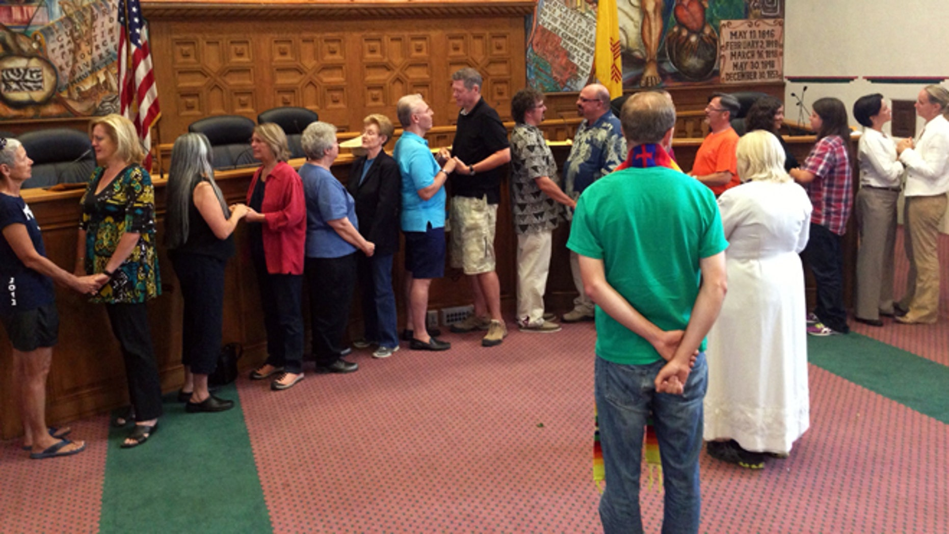 Nine same-sex couples take their wedding vows in the Santa Fe County Commission's chambers after receiving marriage licenses in Santa Fe, N.M., on Friday, Aug. 23. The Rev. Talitha Arnold, in white in foreground, of the United Church of Santa Fe officiated the ceremony. (AP Photo/Barry Massey)