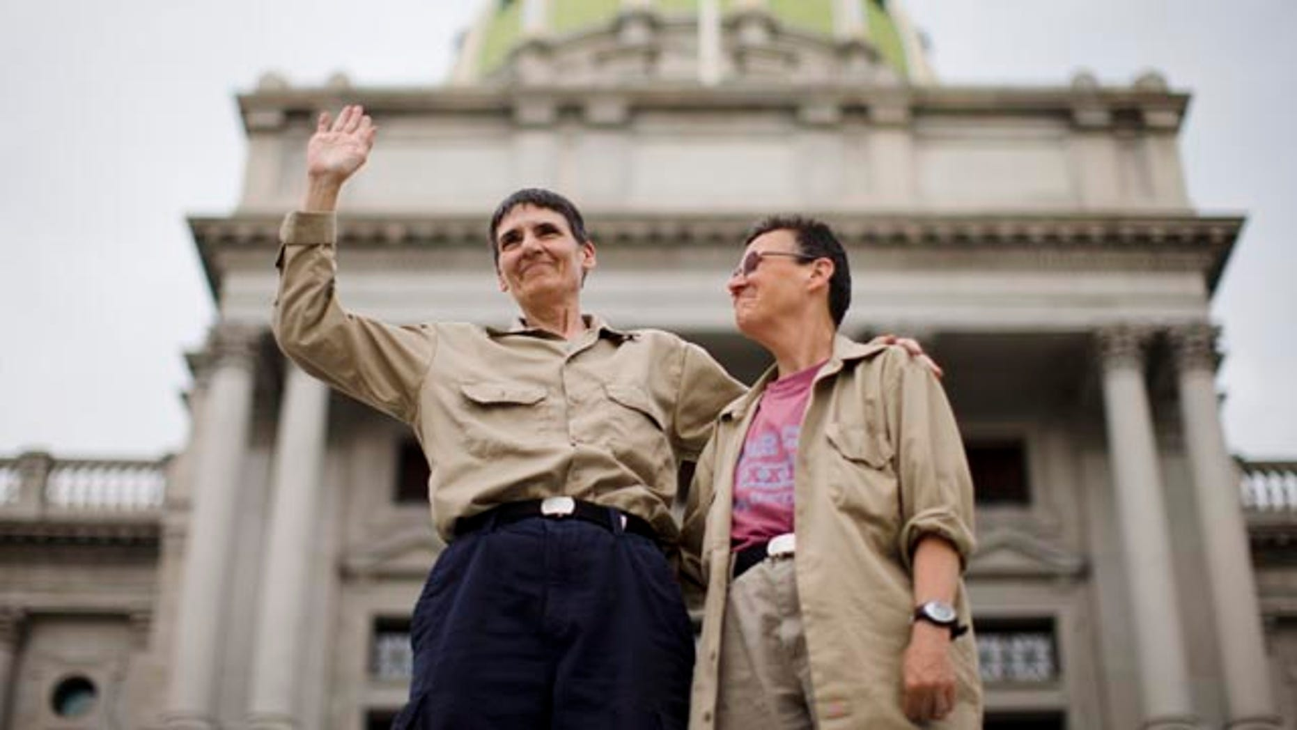 May 20 ,2014: Julie Lobur, left, and Marla Cattermole look out on supporters of gay marriage at a rally on the steps of the state Capitol. (AP Photo/Matt Rourke)