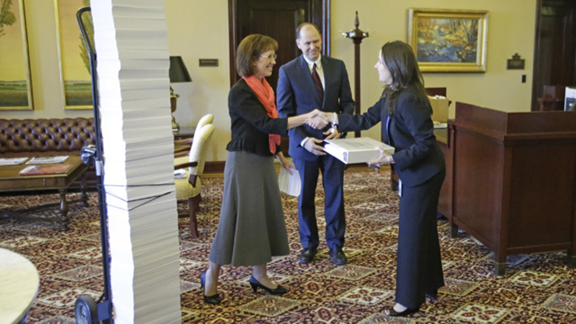 September 5, 2014: Opponents of same-sex marriage Laura Bunker, left, with the United Families International and Bill Duncan, of the Sutherland Institute, give Tiffany Clason, right, an employee of Gov. Gary Herbert's office, a list of 18,600 names of people who signed online petitions supporting traditional marriage and Utah's defense of its gay marriage ban during a meeting at the Utah State Capitol in Salt Lake City. (AP Photo/Rick Bowmer)
