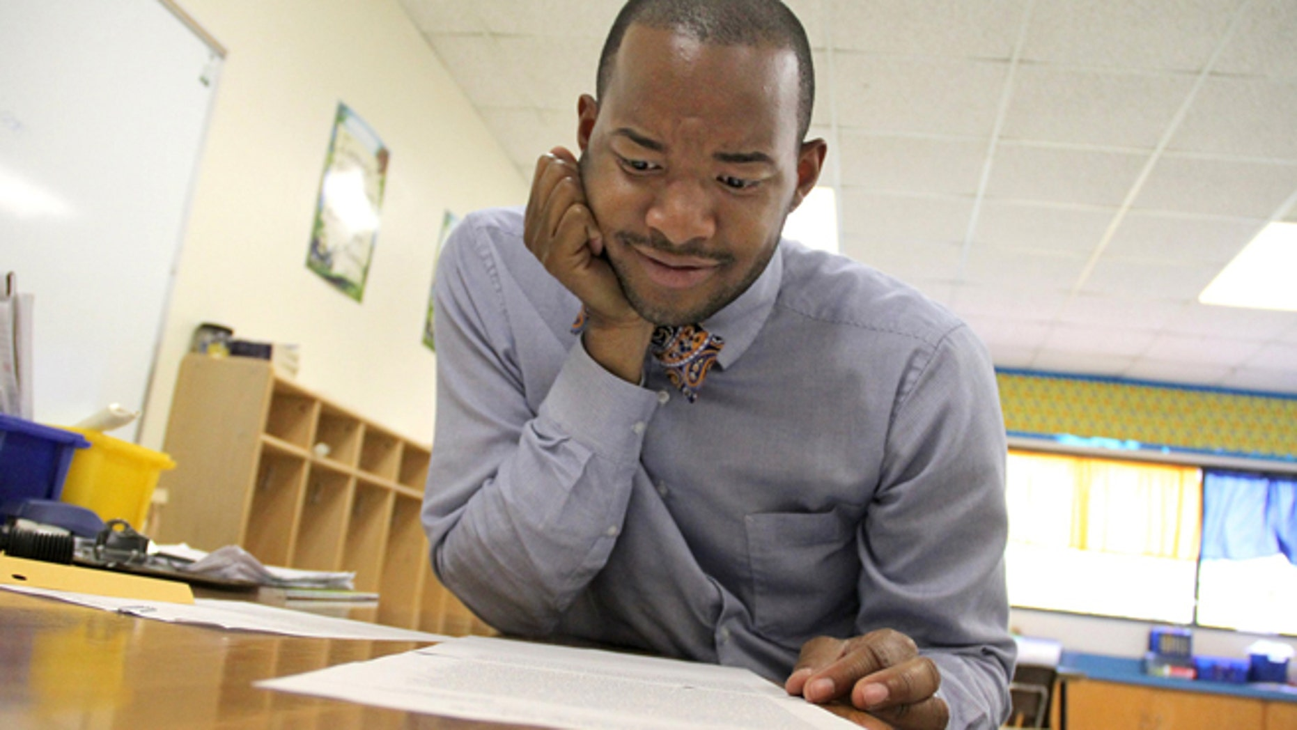 "In this May 27, 2015 photo, teacher Omar Currie reads a copy of a complaint a parent filed about him reading the book ""King & King to his third-graders in Efland, N.C."