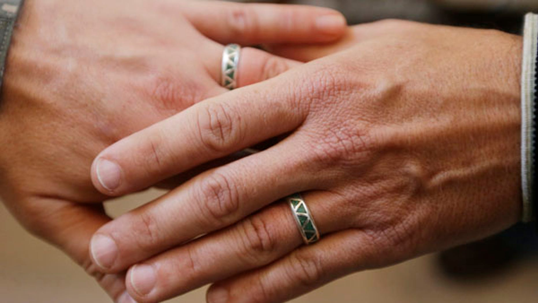 June 29, 2013: Army Capt. Michael Potoczniak, left, and Todd Saunders, of El Cerrito, Calif., show their wedding rings after they exchanged vows at City Hall in San Francisco.