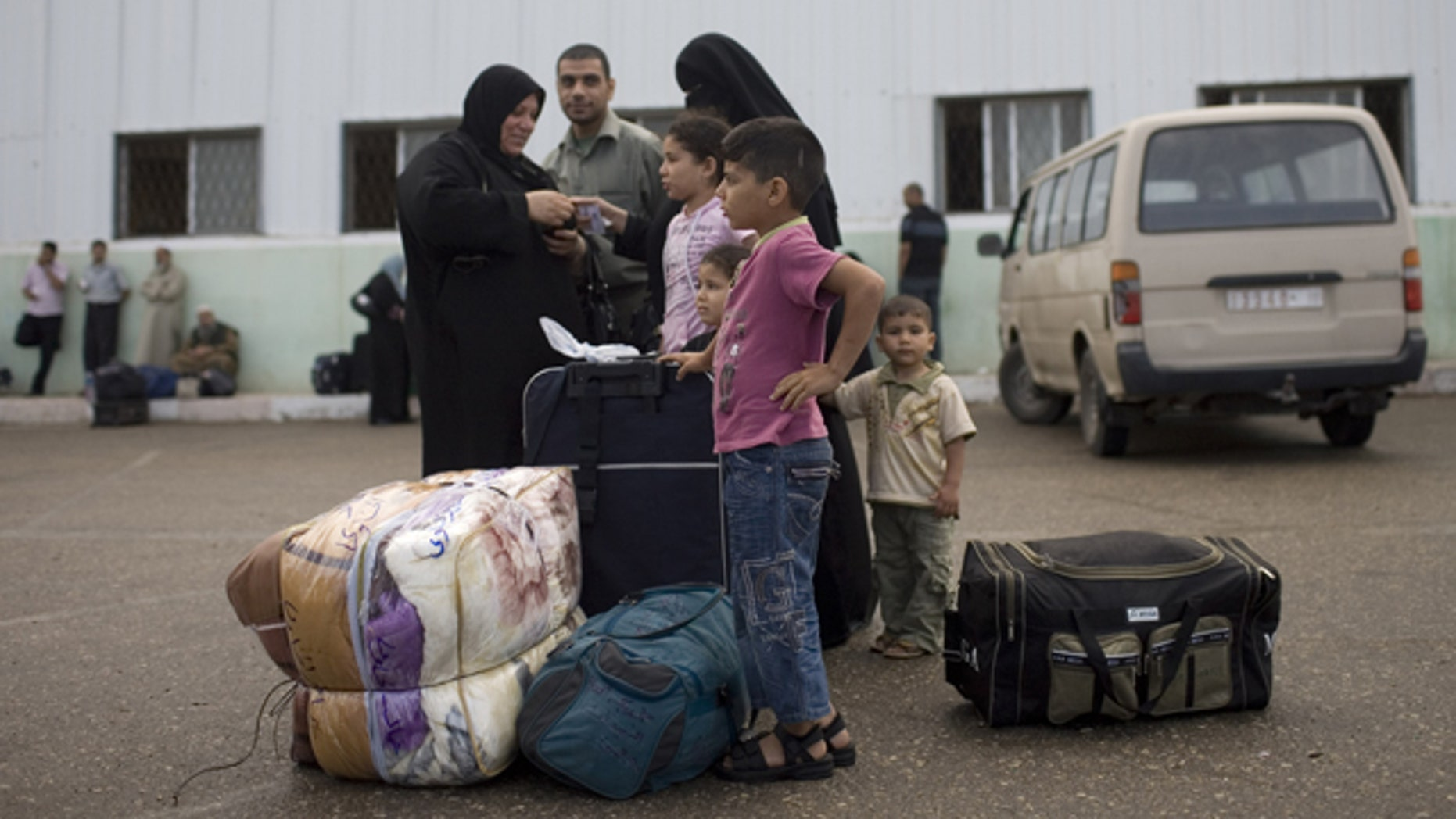 May 28, 2011: A Palestinian family waits before crossing into Egypt through the Rafah border crossing, southern Gaza Strip. After four years, Egypt on Saturday permanently opened the Gaza Strip's main gateway to the outside world, bringing long-awaited relief to the territory's Palestinian population and a significant achievement for the area's ruling Hamas militant group.
