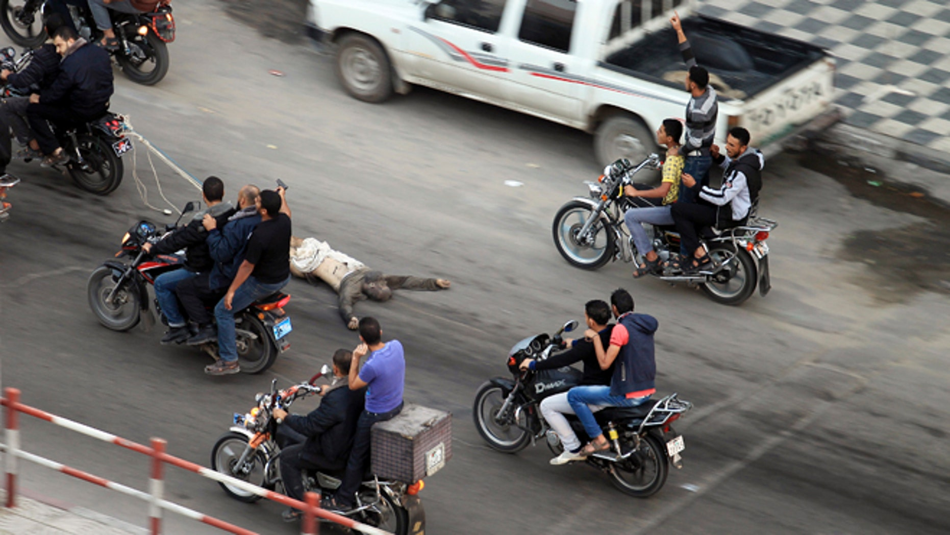 Nov. 20, 2012: Palestinian gunmen ride motorcycles in Gaza City as they drag  the body of a man who was suspected of working for Israel.
