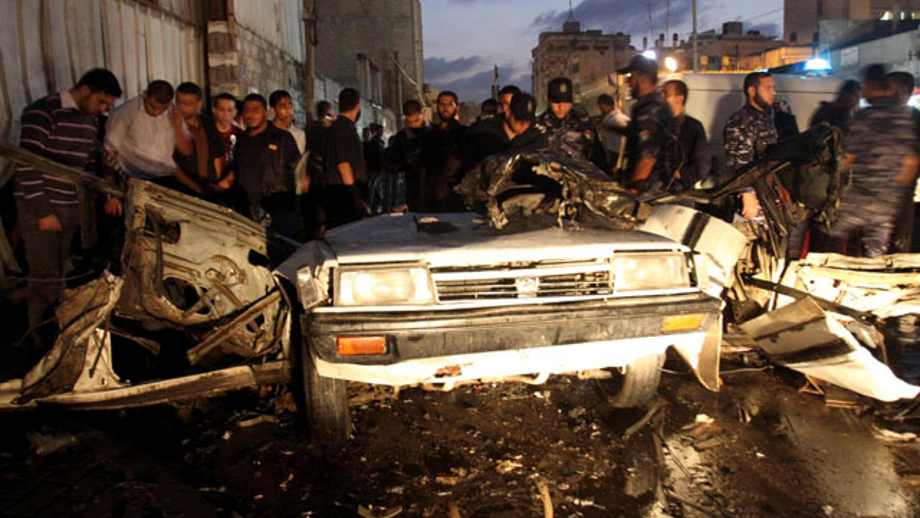 Nov. 17: Palestinians gather around a destroyed car after an explosion in Gaza City.
