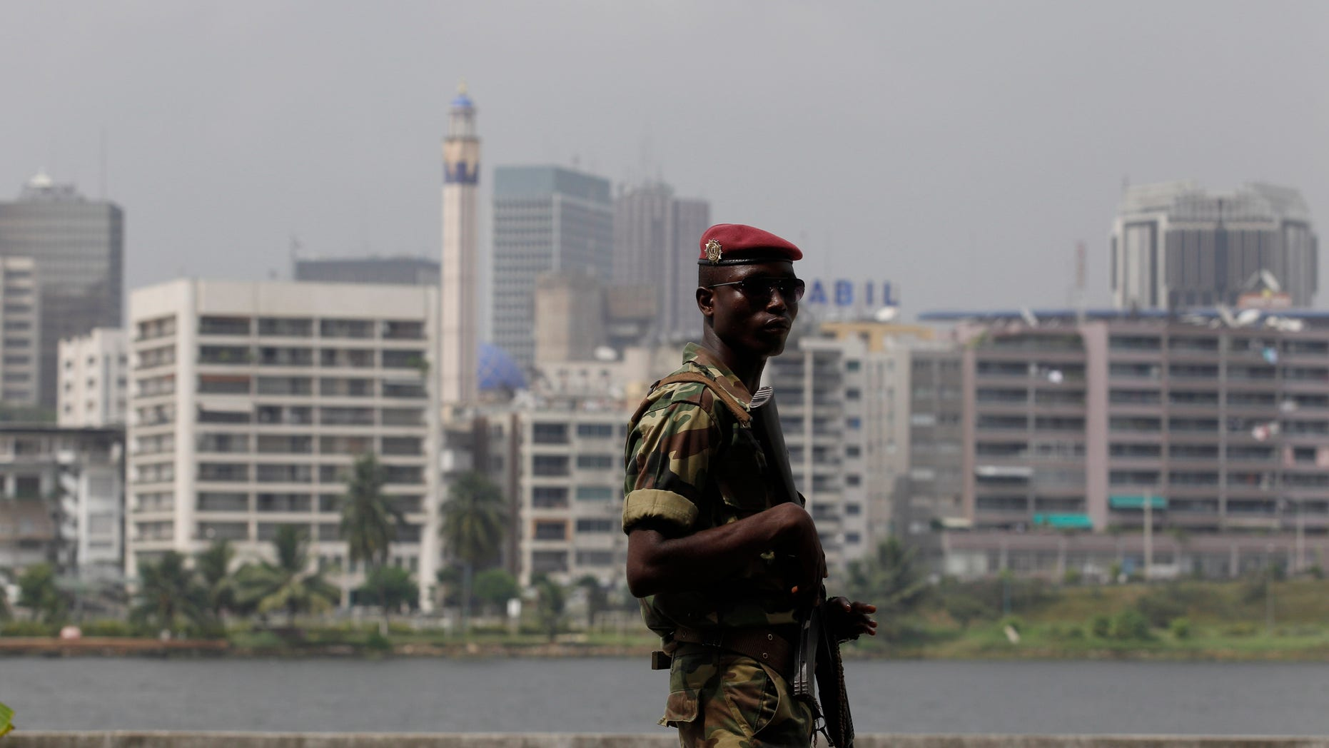 Jan. 9, 2011: Against a backdrop of Abidjan's central Plateau district, a soldier provides security at a rally in support of incumbent president Laurent Gbagbo, at the Palace of Culture in Abidjan, Ivory Coast. Former Nigerian President Olusegun Obasanjo was shuttling between meetings Sunday with the country's defiant president who refuses to cede power and the internationally recognized winner in the latest effort to resolve the post-election crisis. (AP)