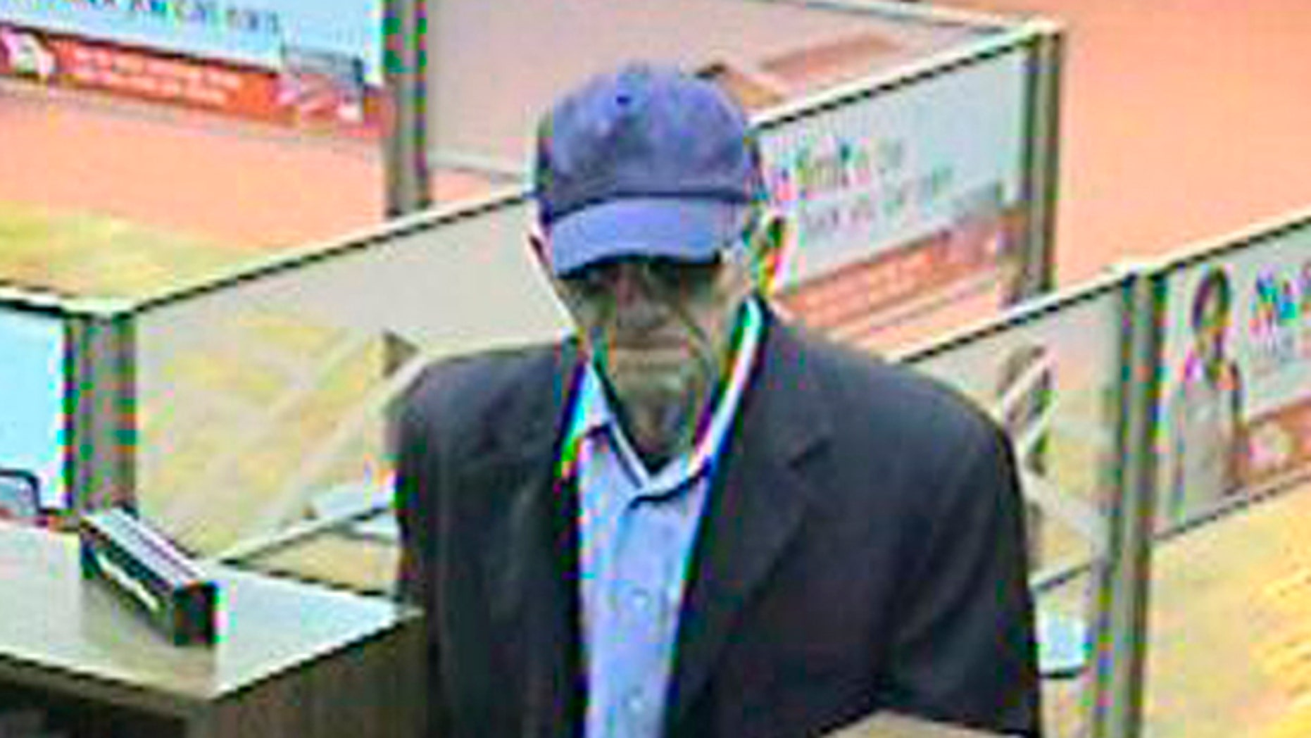 """This image provided by the FBI shows a bank robber, nicknamed, the """"Geezer Bandit"""" robbing a bank in Goleta, Calif"""