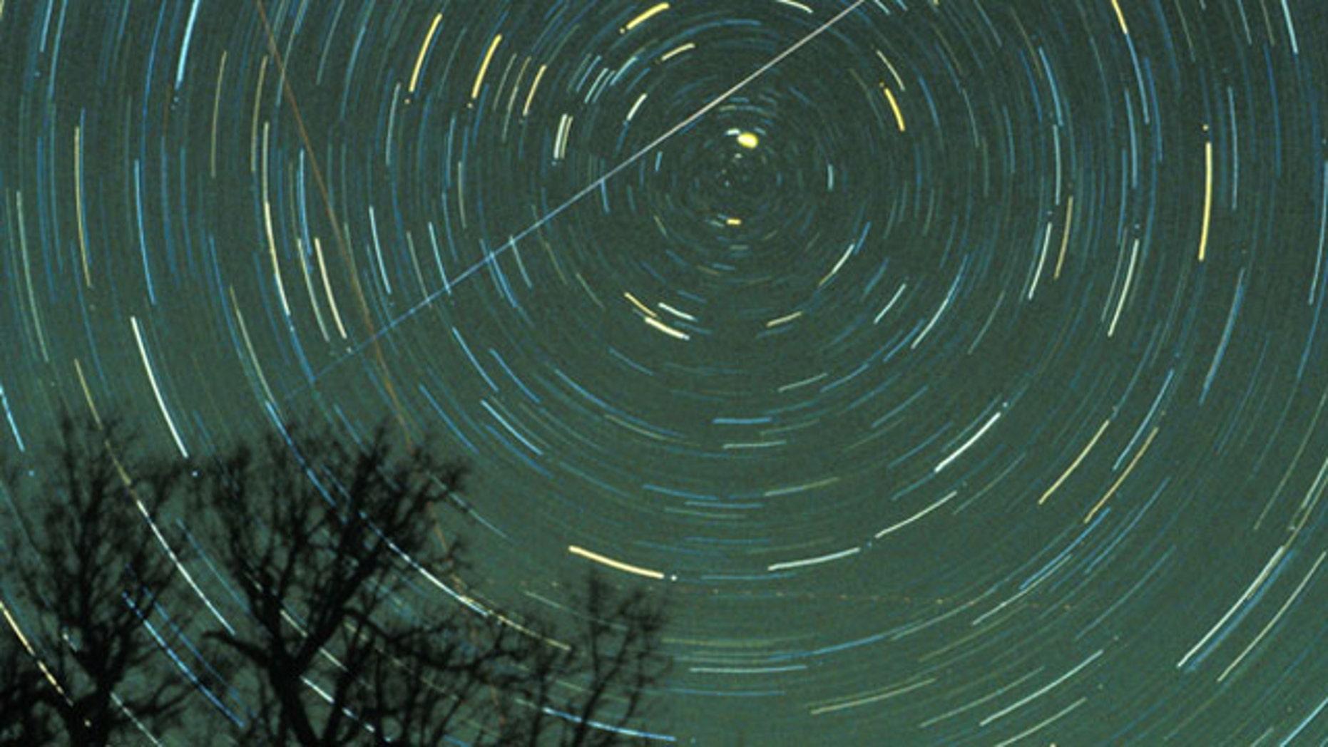 A Geminid meteor streaks across the sky.