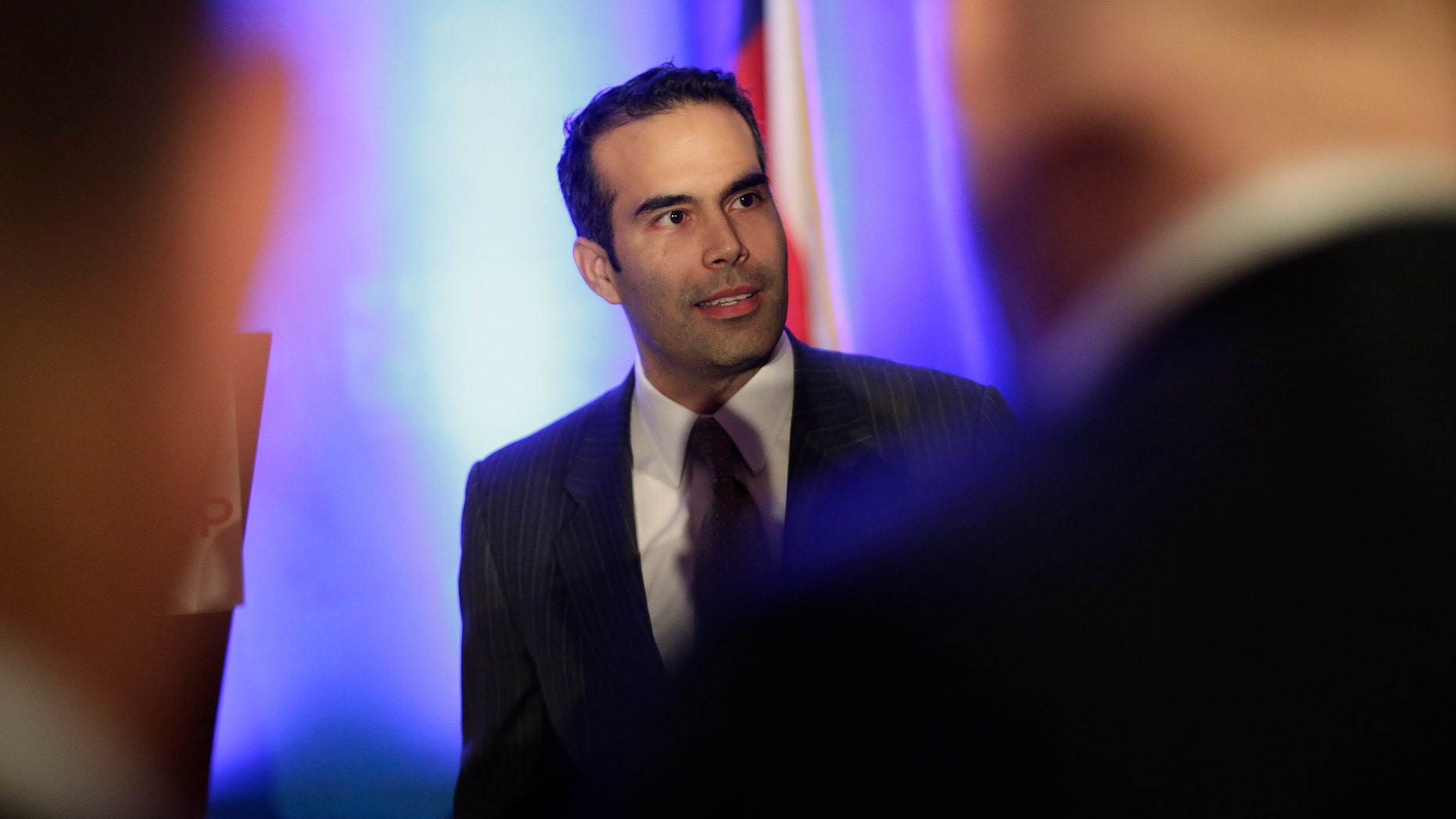 FILE - In this Feb. 26, 2013 file photo, George P. Bush, left, talks to businessmen prior to making the opening statements at the Texas Business Leadership Council in Austin, Texas. Ending months of speculation about what post the grandson of one former U.S. president and nephew of another planned to seek, spokesman Trey Newton told The Associated Press that Bush filed the official paperwork Tuesday, March 12, 2013 to run for land commissioner, a popular stepping stone to higher office.(AP Photo/Eric Gay, File)