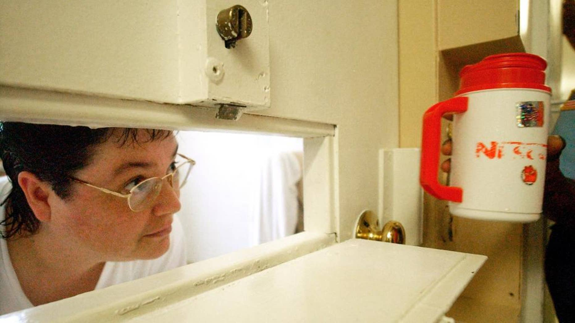 FILE -In this Tuesday, July 6, 2004, file photo, Kelly Gissendaner, the only woman on Georgia's death row, peers through the slot in her cell door as a guard brings her a cup of ice at Metro State Prison in Atlanta. Gissendaner's lawyers, on Monday, March 2, 2015, asked the Georgia State Board of Pardons and Paroles to reconsider her request to have her sentence changed to life in prison. Gissendaner, 46, is set for execution at 7 p.m. (0200 GMT) at the state prison. Gissendaner was convicted of murder in the February 1997 stabbing death of her husband. (AP Photo/Atlanta Journal-Constitution, Bita Honarvar, File)