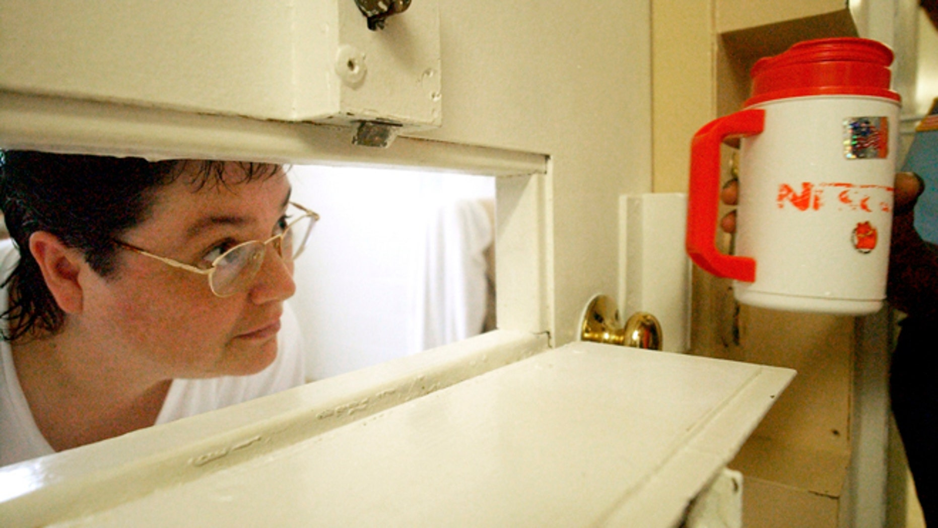 July 6, 2004: In this file photo, Kelly Gissendaner, the only woman on Georgia's death row, peers through the slot in her cell door as a guard brings her a cup of ice at Metro State Prison in Atlanta. (AP/Atlanta Journal-Constitution, Bita Honarvar, File)