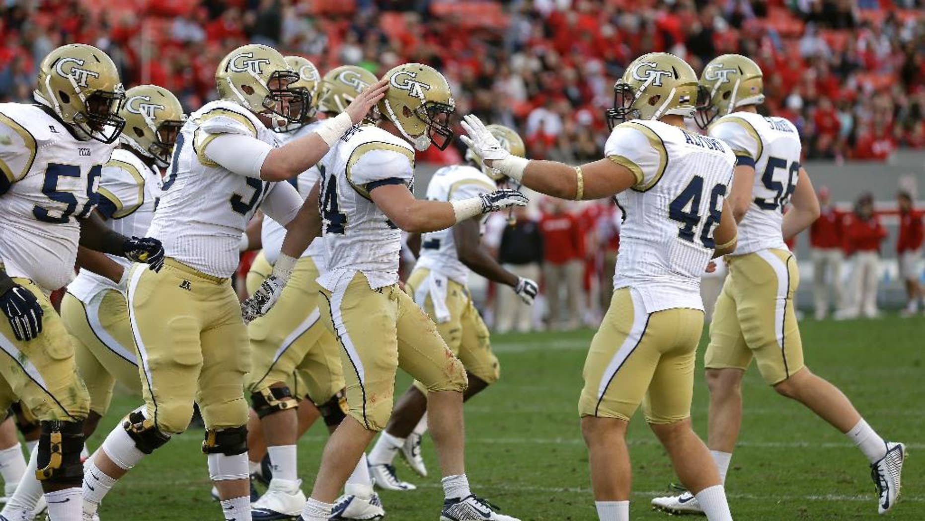 Georgia Tech's Matt Connors, center, is congratulated by teammates following Connors' touchdown against North Carolina State during the second half of an NCAA college football game in Raleigh, N.C., Saturday, Nov. 8, 2014. Georgia Tech won 56-23. (AP Photo/Gerry Broome)