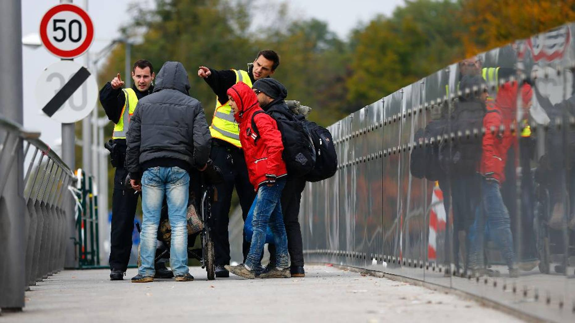 German federal police officers talk to arriving migrants on a bridge at the border between Austria and Germany in Freilassing near Salzburg, Germany, Tuesday, Oct. 13, 2015. (AP Photo/Matthias Schrader)