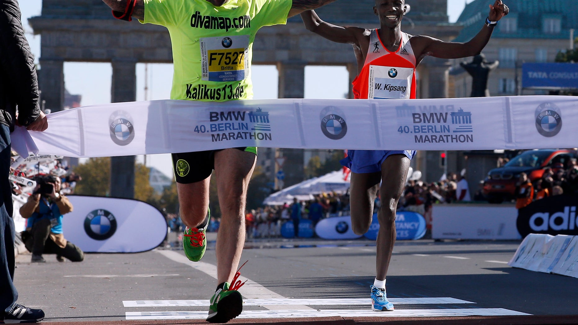 Sept. 29, 2013 - Winner Wilson Kipsang, right, from Kenya smiles as an unidentified man crosses the finish line during the 40th Berlin Marathon in Berlin, Germany. Kipsang set a new world record of 2h 3min 23sec.