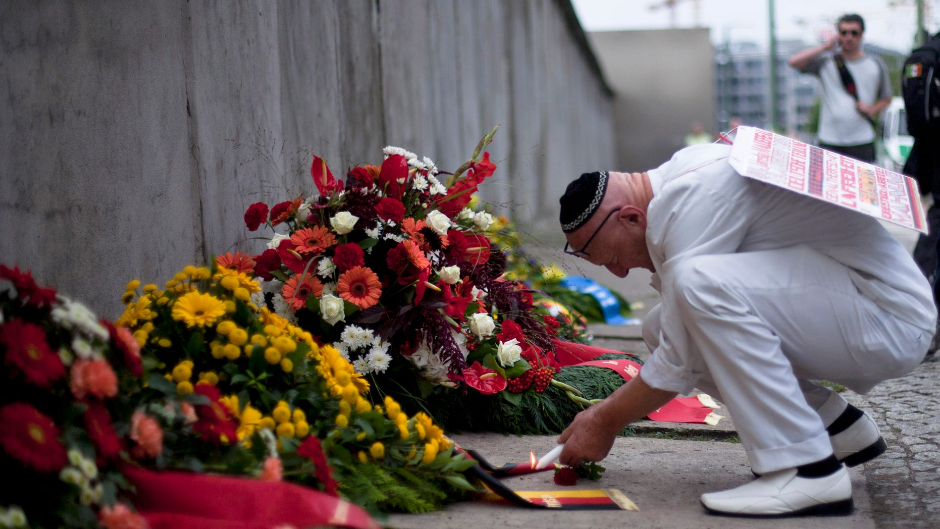 Achim von Almrich lights a candle at the Berlin Wall Memorial at Bernauer Strasse in Berlin, Saturday, Aug. 13, 2011.