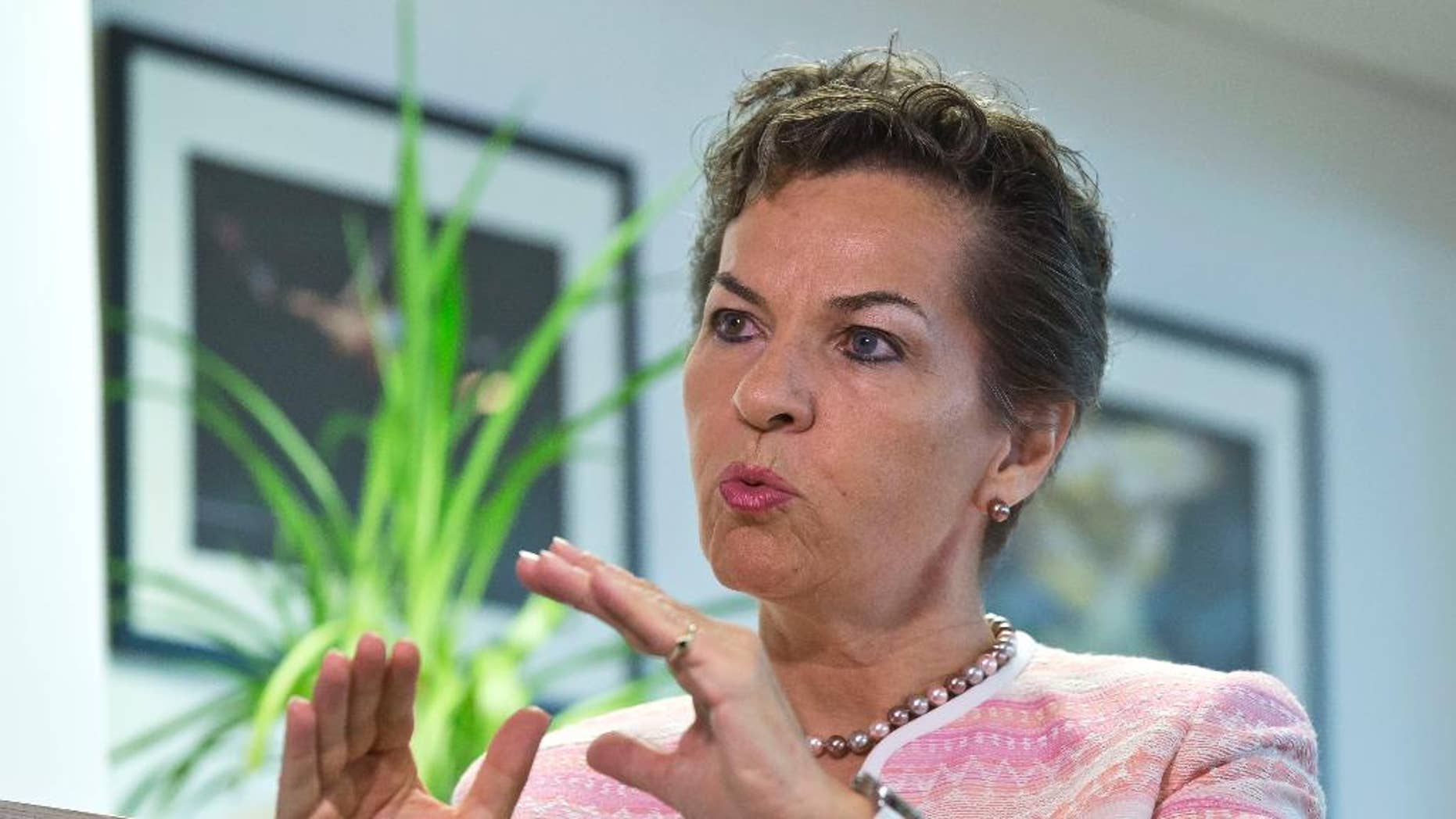 FILE - In this July 22, 2015 file photo United Nations climate chief Christiana Figueres, gestures as she speaks during an interview of the Associated Press in Paris, France. Figueres says Friday, Oct. 30, 2015, emissions-cutting pledges made by governments ahead of a December conference are a good step toward achieving an international global-warming goal, but they aren't yet enough. (AP Photo/Michel Euler, file)