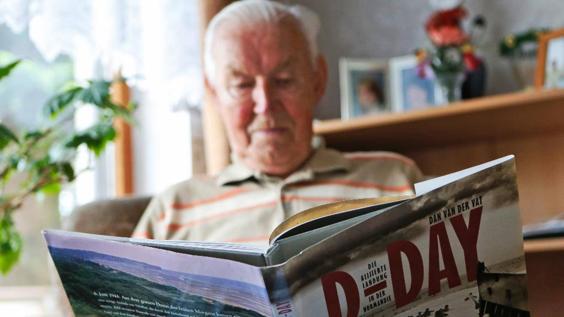 May 28,2014: In this file picture, Germany' s World War 2 and D-Day veteran Paul Golz reads in a book during an interview with the Associated Press in his hometown Koenigswinter, Germany. Paul Golz, one of a few German veterans who plans to attend this week's events marking the 70th anniversary of the D-Day invasion, recalls the generosity of an Allied soldier in Normandy and his luck at being taken prisoner by Americans instead of being sent to fight on the eastern front.