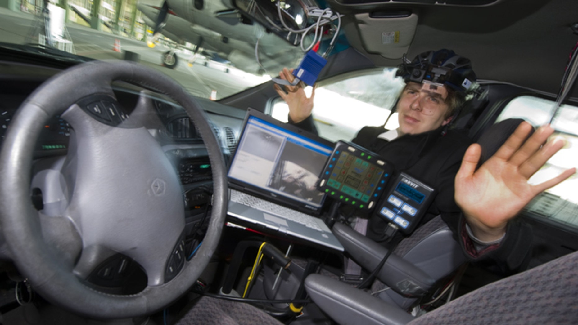 """Scientist David Latotzky of Freie Universitaet Berlin sits on the passenger seat of a car turning the steering wheel with his eye movements in Berlin, Friday, April 23, 2010. The scientists developed the software """"EyeDriver"""" to steer their car """"Spirit of Berlin"""" just by movement of the eyes."""