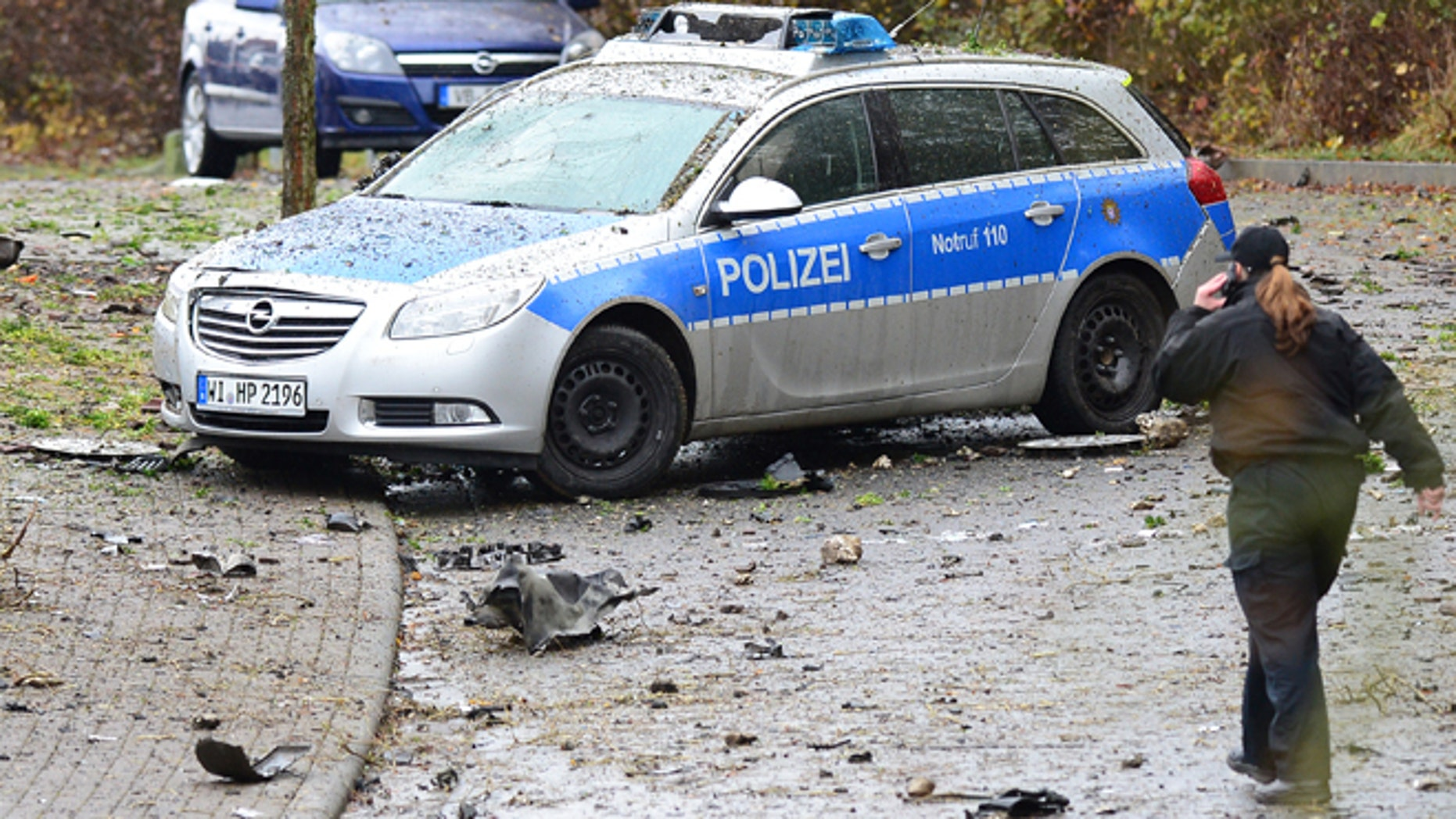 Nov. 16, 2014: A police woman passes a destroyed police car near Homberg  Germany. (AP/dpa,Boris Roessler)