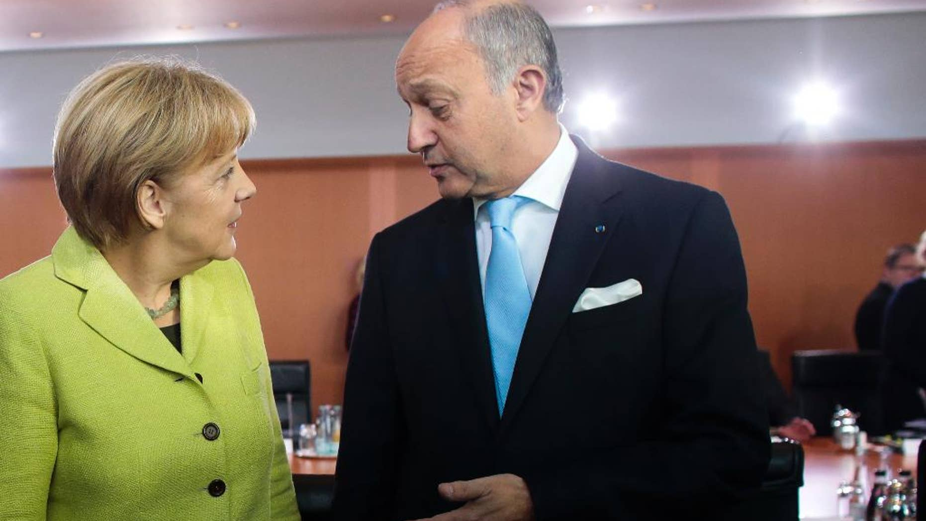 German Chancellor Angela Merkel, left, welcomes France Foreign Minister Laurent Fabius, right, for the German government's cabinet meeting at the chancellery in Berlin, Wednesday, Oct. 15, 2014. Laurent Fabius attends the cabinet meeting as a guest. (AP Photo/Markus Schreiber)