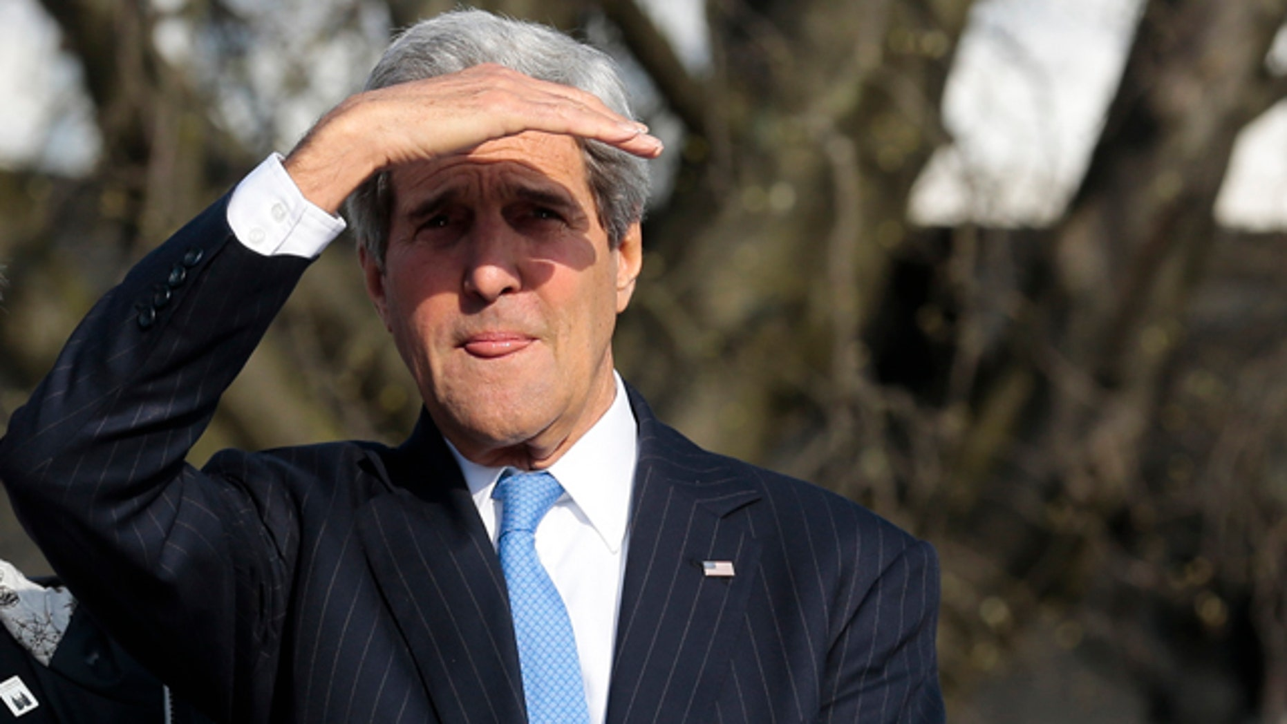 April 15, 2015: United States Secretary of State John Kerry shields his eyes against the sun as he uses a boat on his way to a working session during a meeting of the G7 Foreign Ministers in Luebeck, Germany. The meeting is being held ahead of the G7 leaders summit in Germany from June 7 to 8, 2015. (AP Photo/Markus Schreiber)