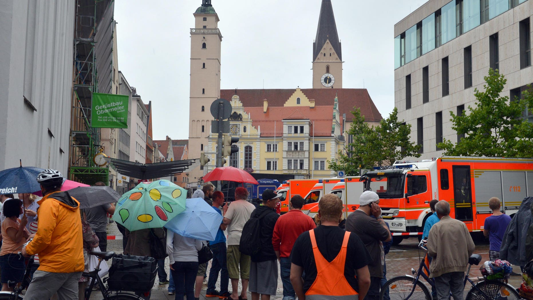 Aug. 19, 2013 - Onlookers stand in front of city hall in Ingolstadt, Germany, after a man took several hostages. Police spokesman Guenther Beck said it wasn't clear what weapons the man might have or what he wants.