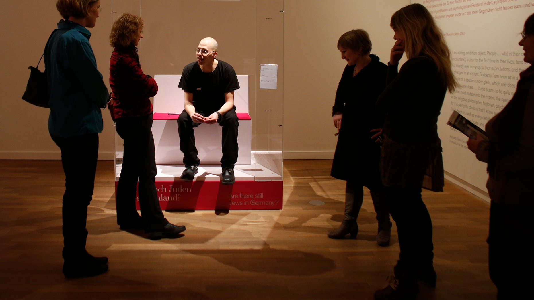 """March 22, 2013 FILE photo: Visitors surround Ido Porat, the 1st person acting as the """"Jew in a glass box,"""" at the exhibition """"The Whole Truth- everything you always wanted to know about Jews"""" at the Jewish Museum in Berlin."""