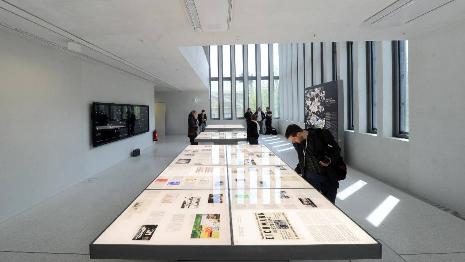 Visitors stand in an exhibition room where exhibits are shown on wall charts and light tables during a press preview of the Documentation Center for the History of National Socialism in Munich, Germany, Wednesday, April 29, 2015. new museum dedicated to exploring its past as the birthplace of the Nazi movement. (Tobias Hase/dpa via AP)