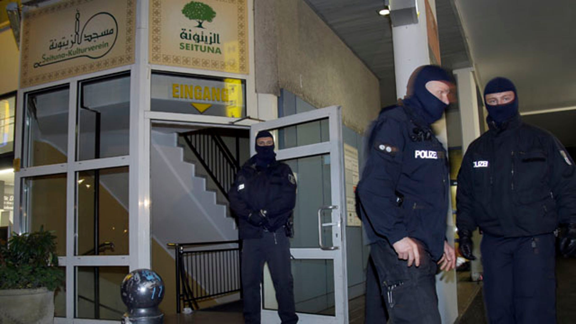 Nov. 26, 2015: Masked police officers guard the 'Seituna' cultural center in Berlin, Germany. Police raided the mosque after the arrest of two people suspected of belonging to an Islamist extremist group. (AP Photo/Michael Sohn)