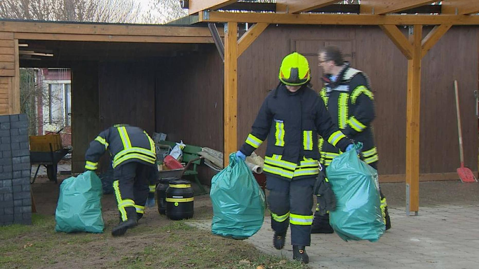 """Firefighters carry plastic bags in a garden in Preetz near Kiel, northern Germany, Tuesday afternoon, Feb. 24, 2015. Workers clearing a small garden property in northern Germany got a shock when they unearthed a rusted can labeled """"Zyklon B"""" _ the deadly poison gas used by the Nazis in the death chambers of Auschwitz and other camps. Emergency crews were able to determine the can was empty, but still sealed it and removed it as a precaution. (AP Photo/dpa, Daniel Friederichs)"""