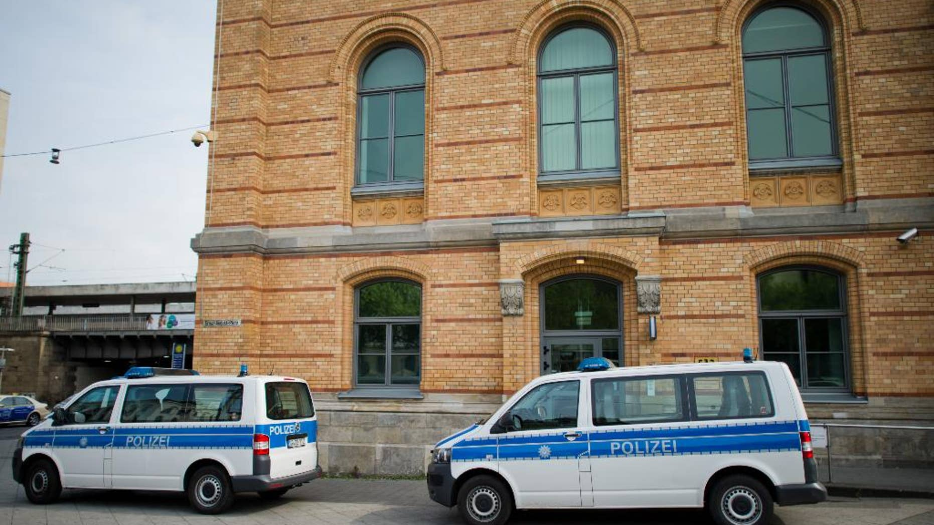 Police cars park in front of the police station at the railway station in Hannover, Germany, Monday, May 18, 2015. Hannover prosecutors said a 39-year-old police officer is being investigated on allegations he abused two immigrants while they were in custody and boasted about it over social media.  (Julian Stratenschultedpa via AP)