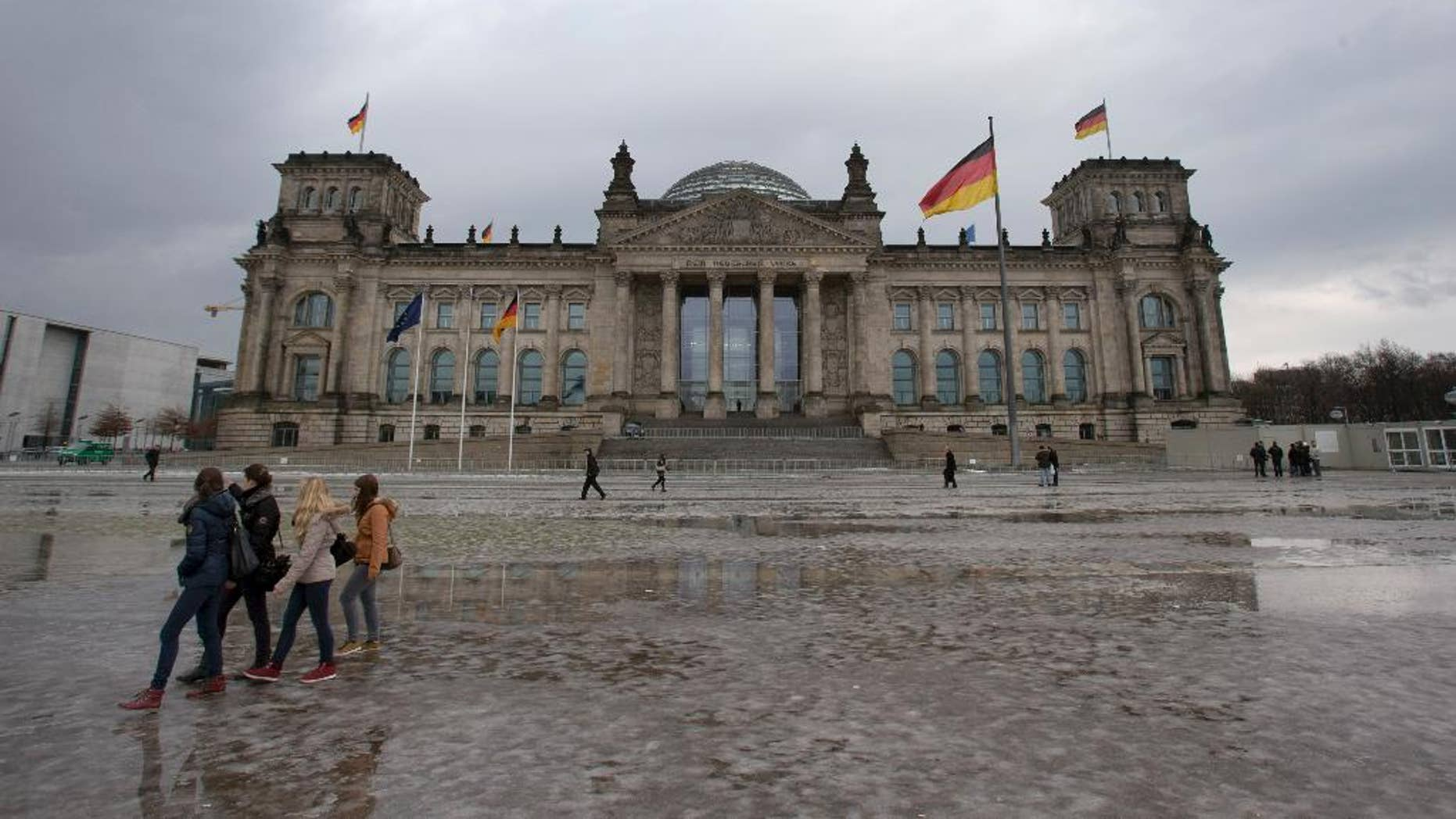 FILE - In this Jan. 29, 2013, file photo visitors walk past the Reichstag building, host of the German federal parliament Bundestag, in Berlin Germany. Berlin police say an unidentified person threw a Molotov cocktail onto the steps of the capital's landmark Reichstag but failed to start a blaze. The person threw the bottle full of a flammable liquid at a side entrance of the building early Monday morning, Sept. 29, 2014, police said. They say the liquid ignited for a short time and then sputtered out, and the attacker fled on foot. Nobody was injured. (AP Photo/Michael Sohn, File)