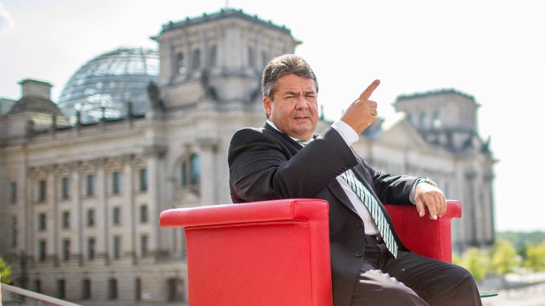 """German  vice chancellor and Minister for Economy,  Sigmar Gabriel  attends an interview by German  TV channel  ARD in Berlin, Sunday July 27, 2014.  In background the parliament building 'Reichstag' . Germany's vice chancellor says Europe should take aim at rich businesspeople who support Russia's government as  it increases pressure on Moscow over its actions in Ukraine. Sigmar  Gabriel, who is also Germany's economy minister, told ARD television Sunday that measures should target """"those on whose shoulders the Russian government stands:  the oligarchs, the billionaires.""""   (AP Photo/dpa/Hannibal Hanschke)"""