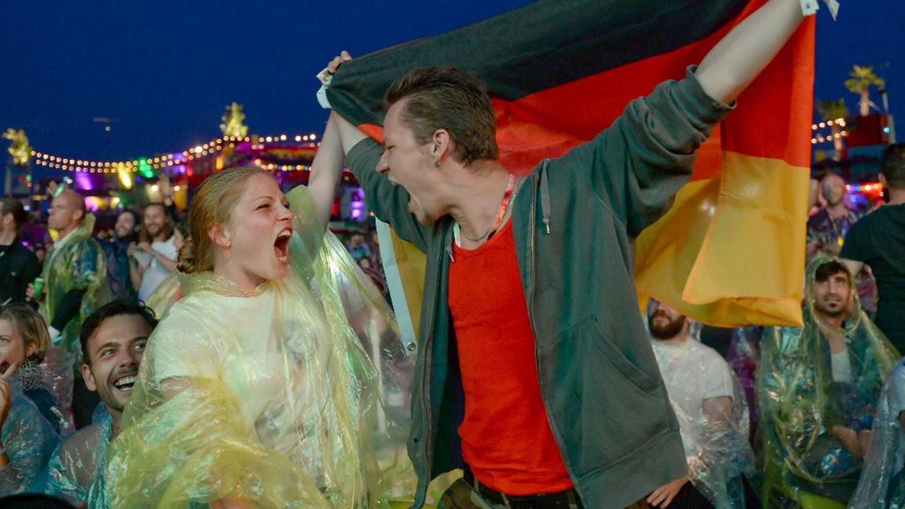 Soccer fans Daniel and Maryan celebrate as they watch the semifinal of the 2014 soccer World Cup between Brazil and Germany on the sidelines of the 'Bread & Butter' fair in Berlin, Tuesday evening, July 8, 2014.  (AP Photo/dpa, Britta Pedersen)