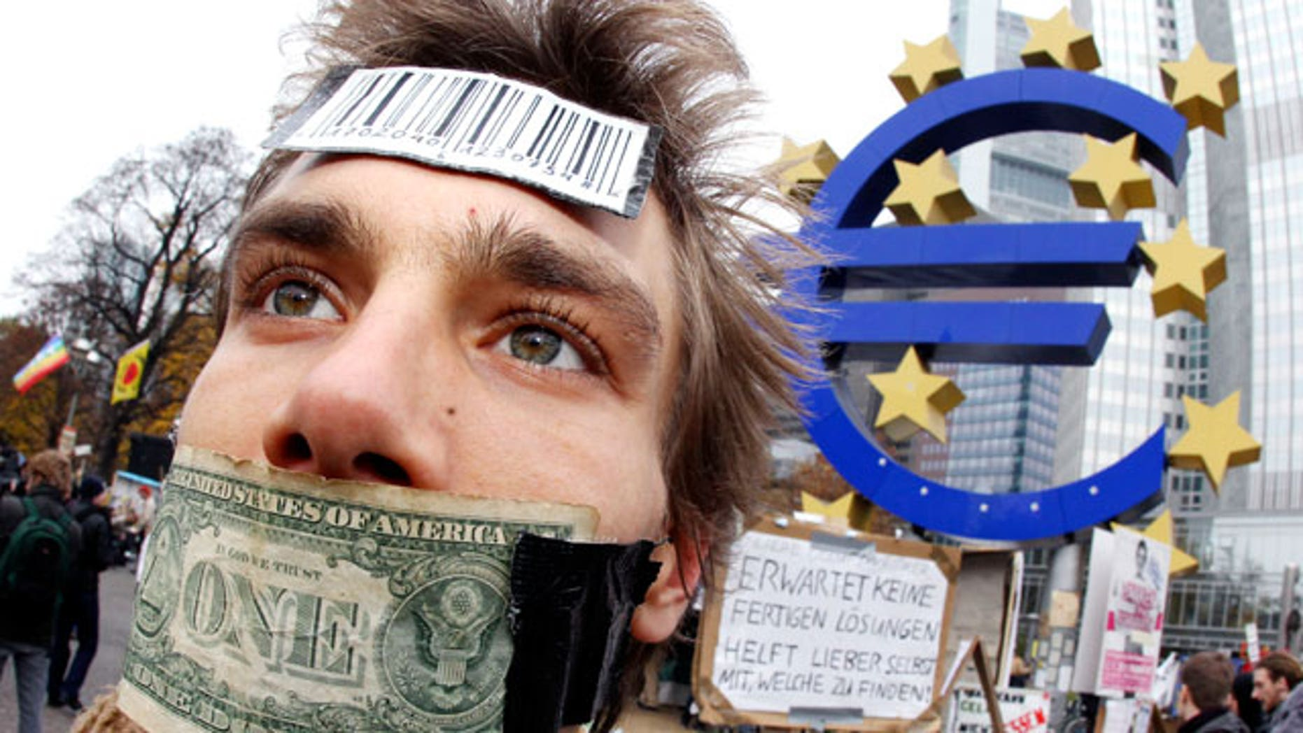 Nov. 12, 2011: A demonstrator has taped his mouth with a dollar bill in front of the European Central Bank in Frankfurt, Germany.