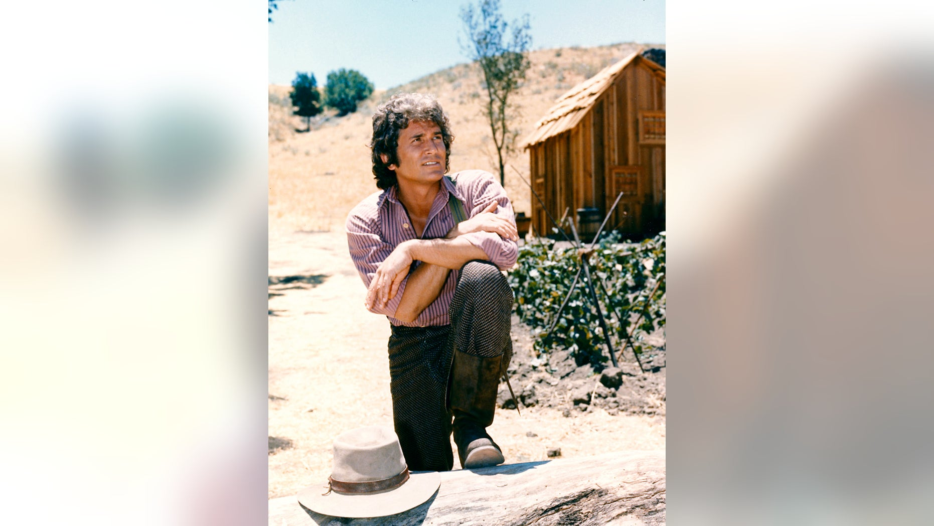 Michael Landon (1936-1991), US actor, poses with his arms crossed and resting on his knee with a log cabin the background in a portrait issued as publicity for the US television series, 'Little House on the Prairie', circa 1974. The drama, adapted from the novels by Laura Ingalls Wilder (1867-1957), starred Landon as 'Charles Ingalls'.