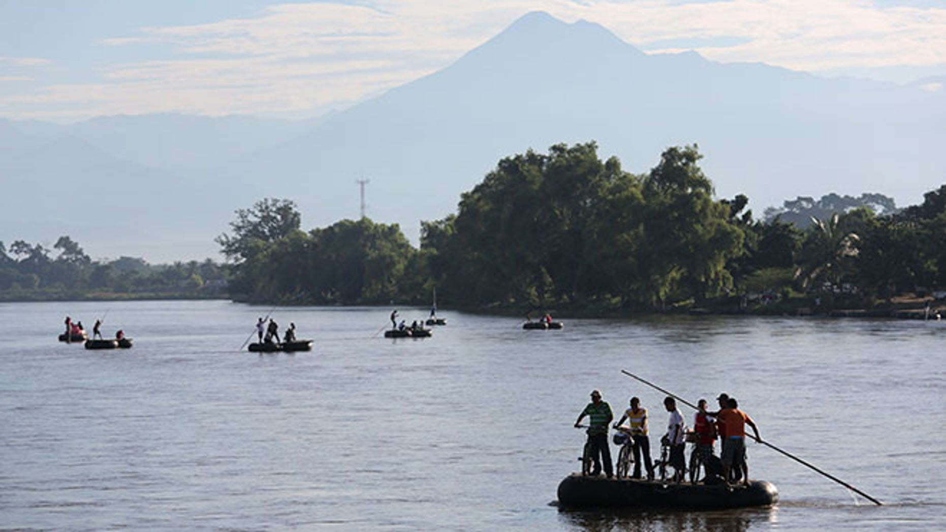 People cross the Suchiate River on rafts from Guatemala into Mexico on August 2, 2013 in Ciudad Hidalgo, Chiapas, Mexico.