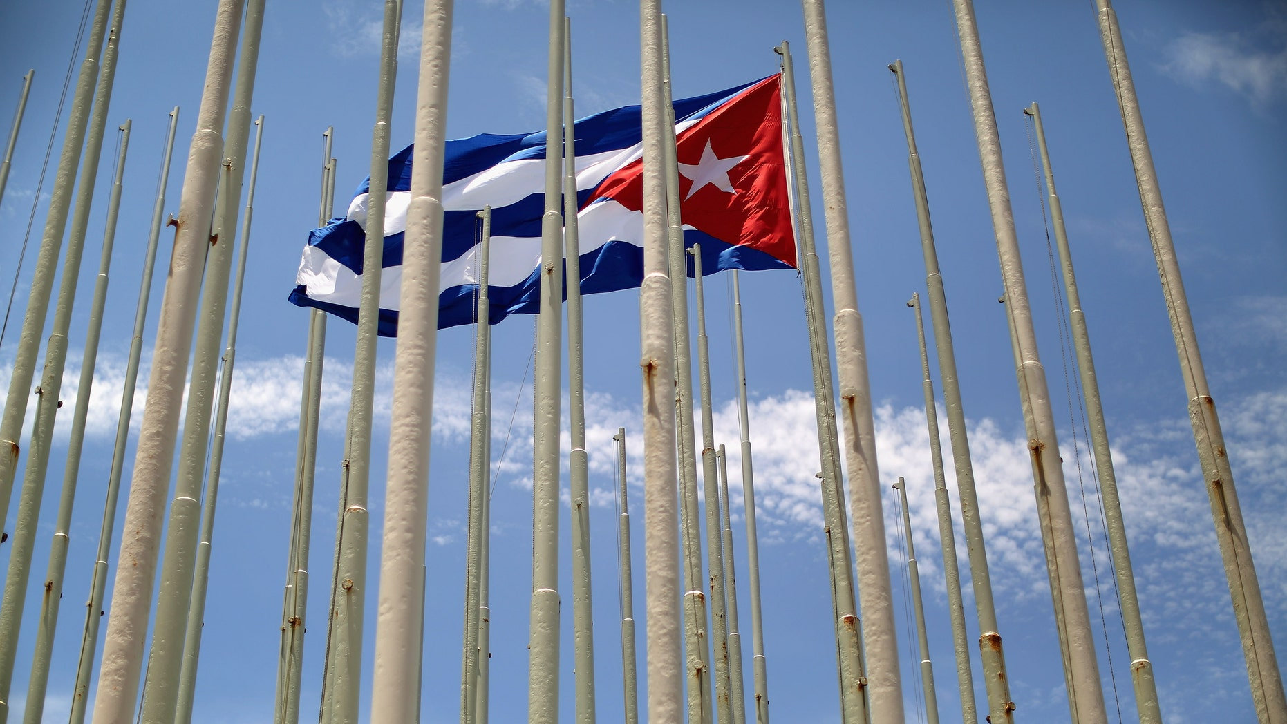 HAVANA, CUBA - AUGUST 13:  A lone Cuban flag is raised inside the 'Wall of Flags' across the street from the U.S. Embassy August 13, 2015 in Havana, Cuba. Cuba planted 138 flag poles in February 2006 in an attempt to obsucre an electronic message ticker on the outside of the U.S. Interests Section building. U.S. Secretary of State John Kerry will visit Havana Friday and raise the American flag at the reopened U.S. embassy, a symbolic act after the the two former Cold War enemies reestablished diplomatic relations in July.  (Photo by Chip Somodevilla/Getty Images)