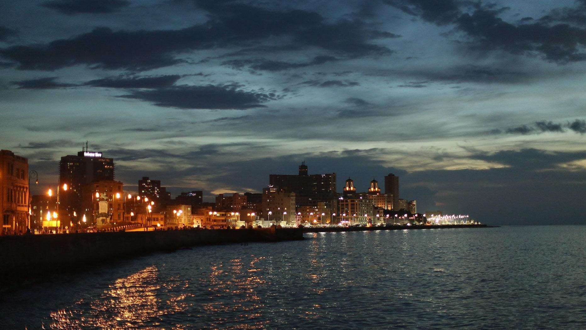 Streetlights along the Malecon seawall boulevard as the sun sets August 14, 2015 in Havana, Cuba.