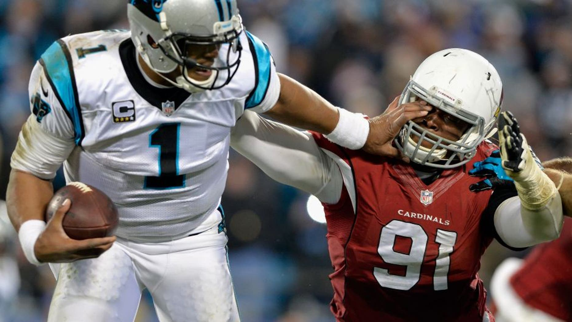 CHARLOTTE, NC - JANUARY 24: Cam Newton #1 of the Carolina Panthers stiff arms Ed Stinson #91 of the Arizona Cardinals in the second half during the NFC Championship Game at Bank of America Stadium on January 24, 2016 in Charlotte, North Carolina. (Photo by Grant Halverson/Getty Images)