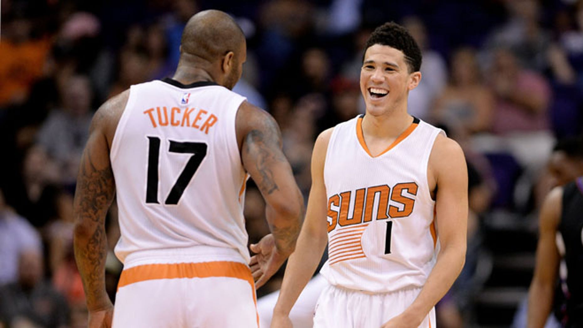 PHOENIX, AZ - APRIL 13:  Devin Booker #1 of the Phoenix Suns smiles in front of teammate P.J. Tucker #17 in the first half of the NBA game against the Los Angeles Clippers at Talking Stick Resort Arena on April 13, 2016 in Phoenix, Arizona.  The Los Angeles Clippers won 114 - 105.  NOTE TO USER: User expressly acknowledges and agrees that, by downloading and or using this photograph, User is consenting to the terms and conditions of the Getty Images License Agreement. (Photo by Jennifer Stewart/Getty Images)