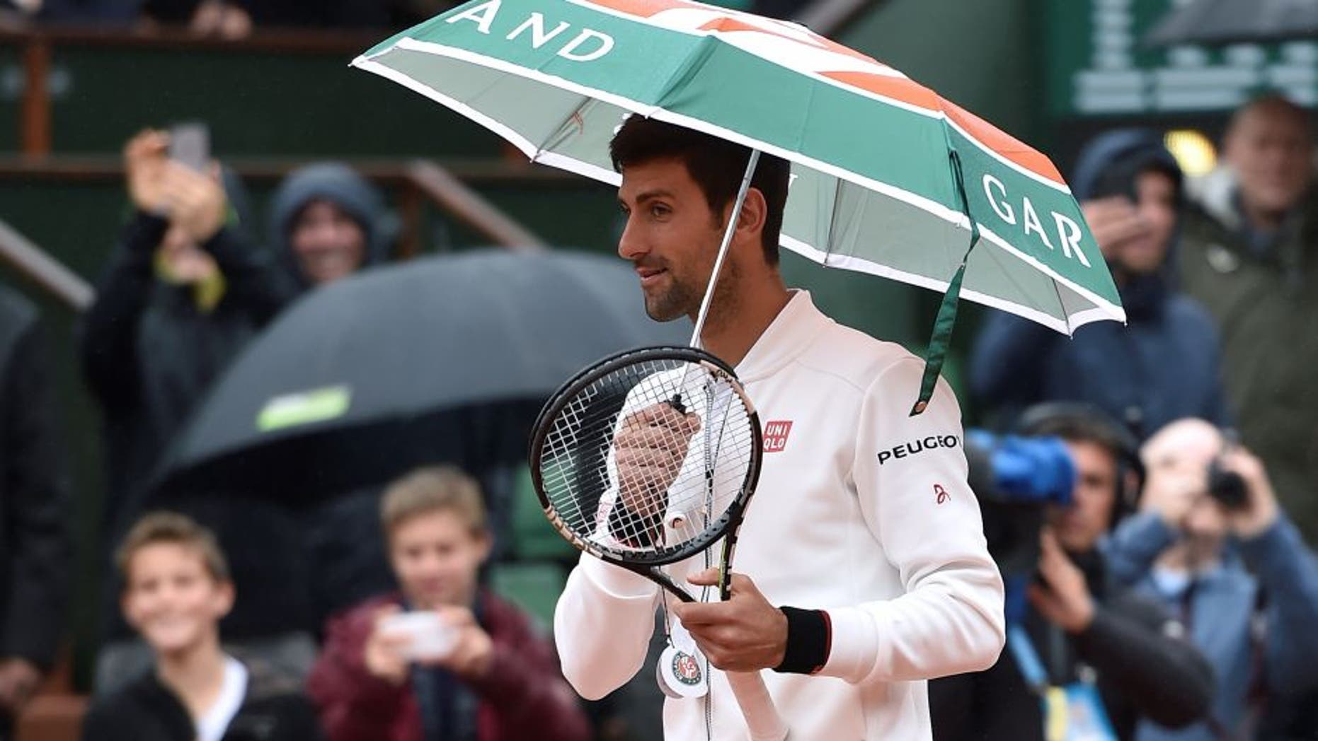 Serbia's Novak Djokovic holds up an umbrella before resuming his men's fourth round match against Spain's Roberto Bautista-Agut at the Roland Garros 2016 French Tennis Open in Paris on May 31, 2016. / AFP / Eric FEFERBERG (Photo credit should read ERIC FEFERBERG/AFP/Getty Images)