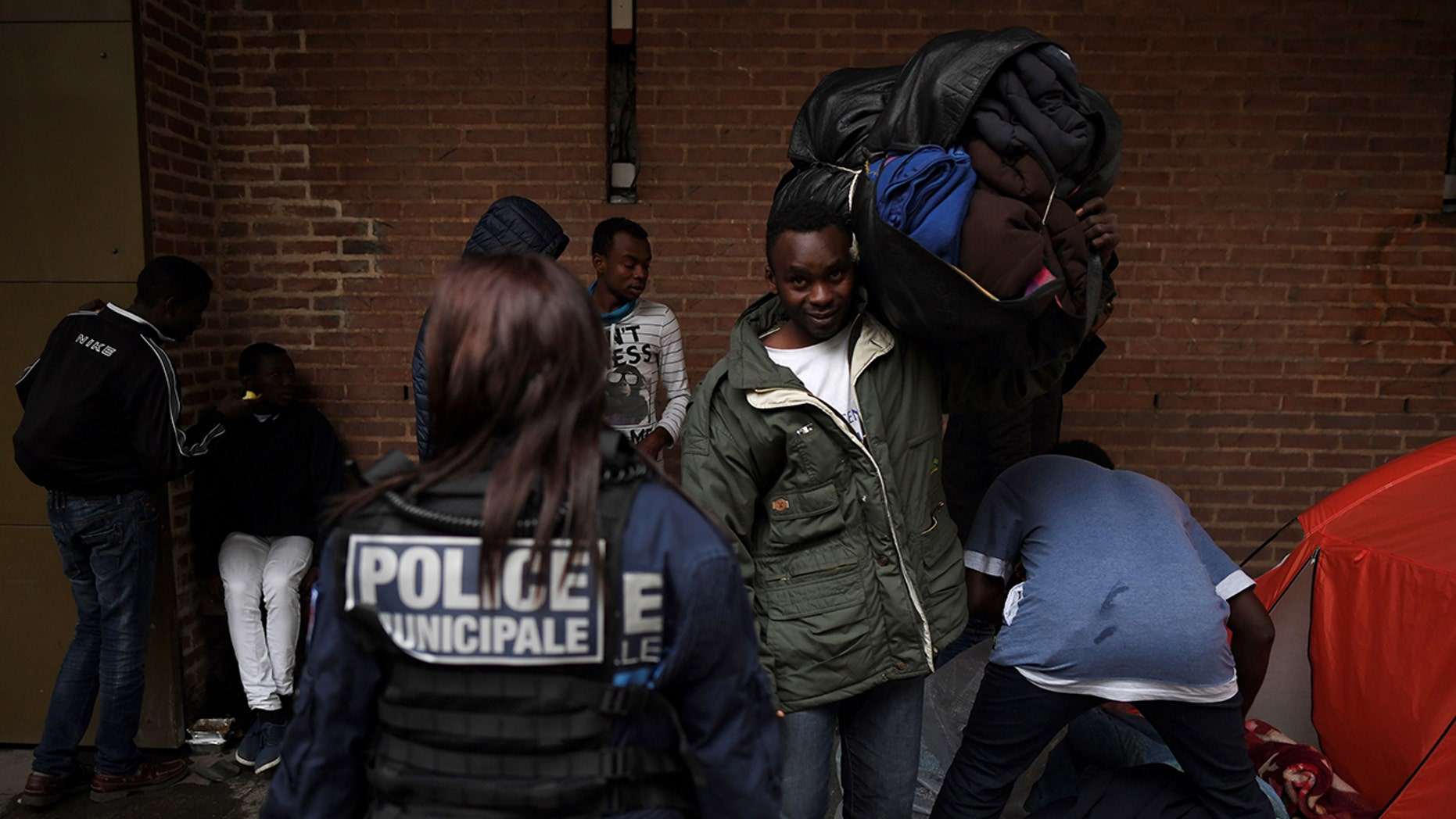 A police officer stands guard as migrants pack up their belongings after sleeping on the floor in Saint-Denis outside Paris on October 11, 2017.