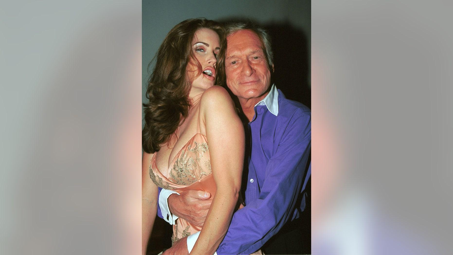 Model Carrie Stevens poses with Playboy founder Hugh Hefner in 2002.