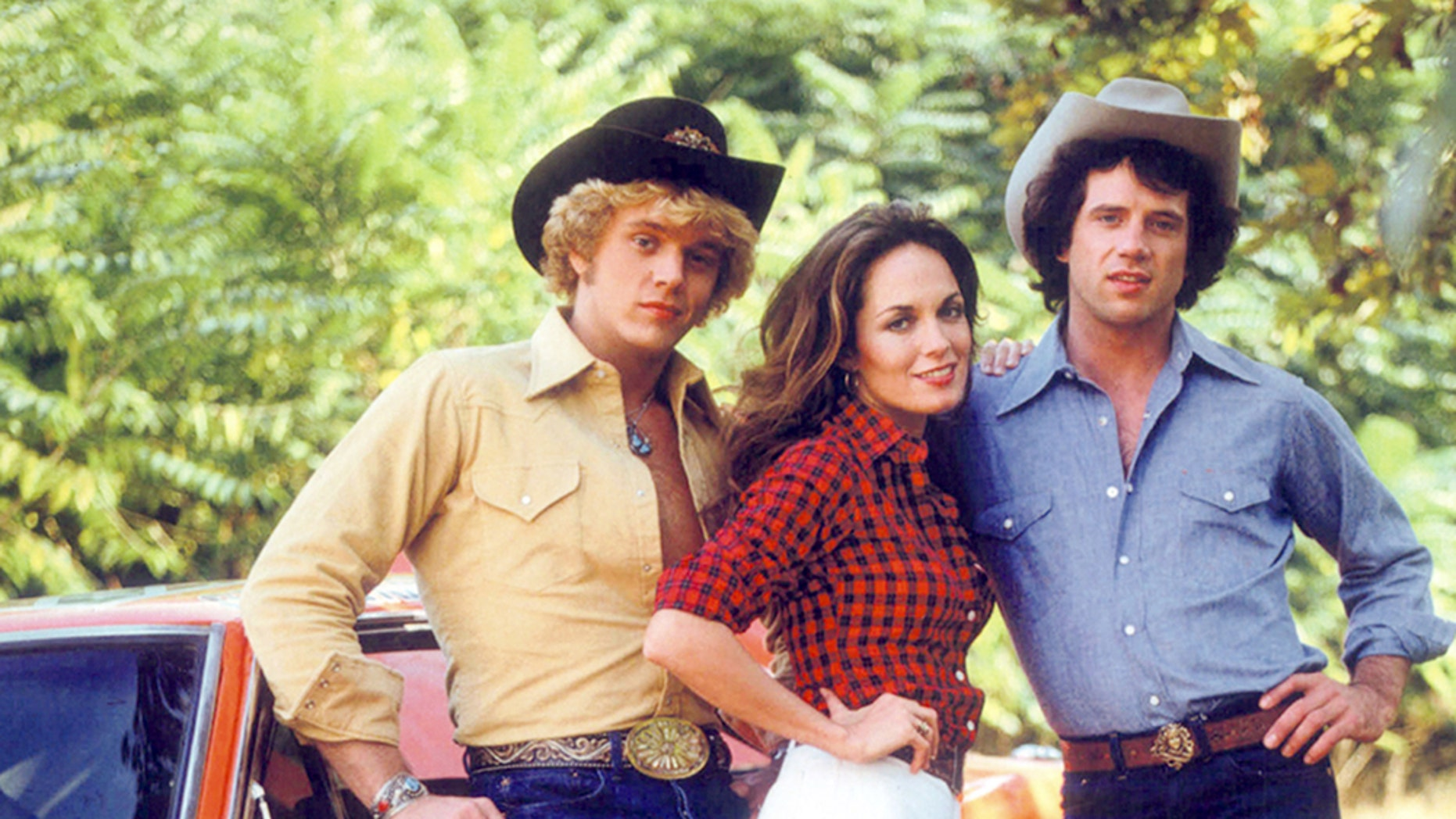 """جان اسنایدر، کاترین باچ و تام ووپت در یک پرتره تبلیغاتی برای نمایش تلویزیونی """"سلطنتی هزاره""""، حدود 1980. آنها به ترتیب بو، دیزی و لوک دوک بازی می کنند."""