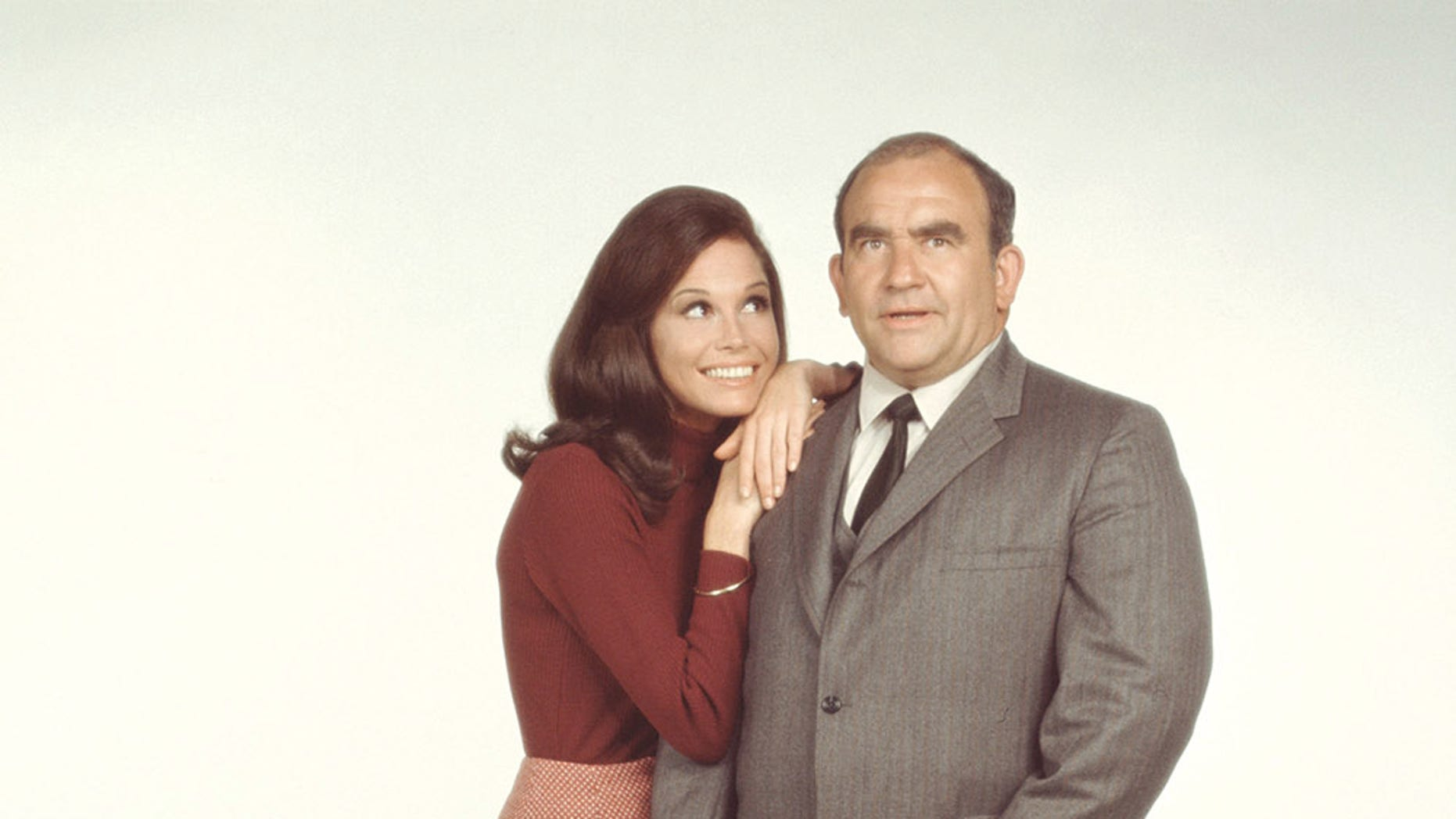 """American actors Mary Tyler Moore, as Mary Richards, and Ed Asner, as Lou Grant, pose for a publicity photo for the CBS comedy, """"The Mary Tyler Moore Show,"""" in 1971."""