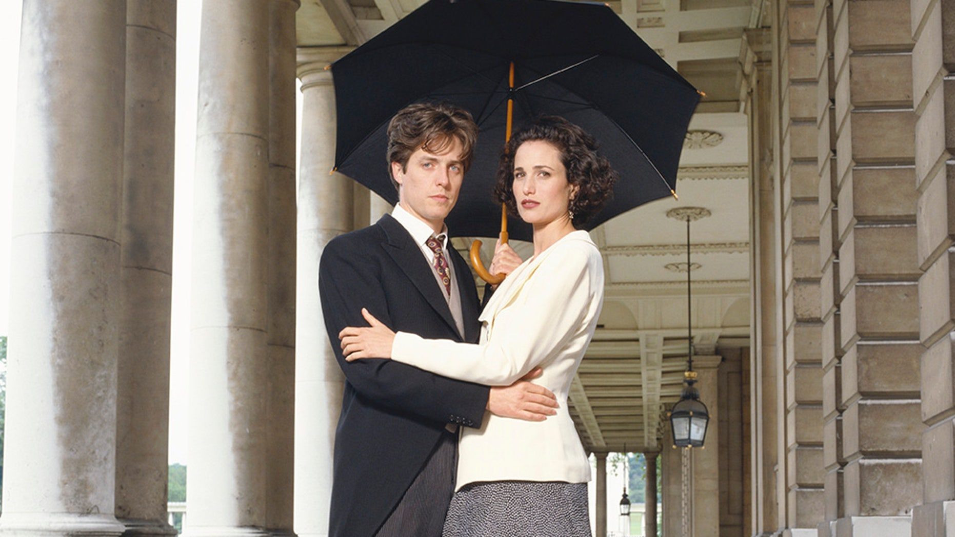 """Actor Hugh Grant and actress Andie MacDowell posing as their characters from Richard Curtis' 1994 comedy """"Four Weddings and a Funeral."""""""