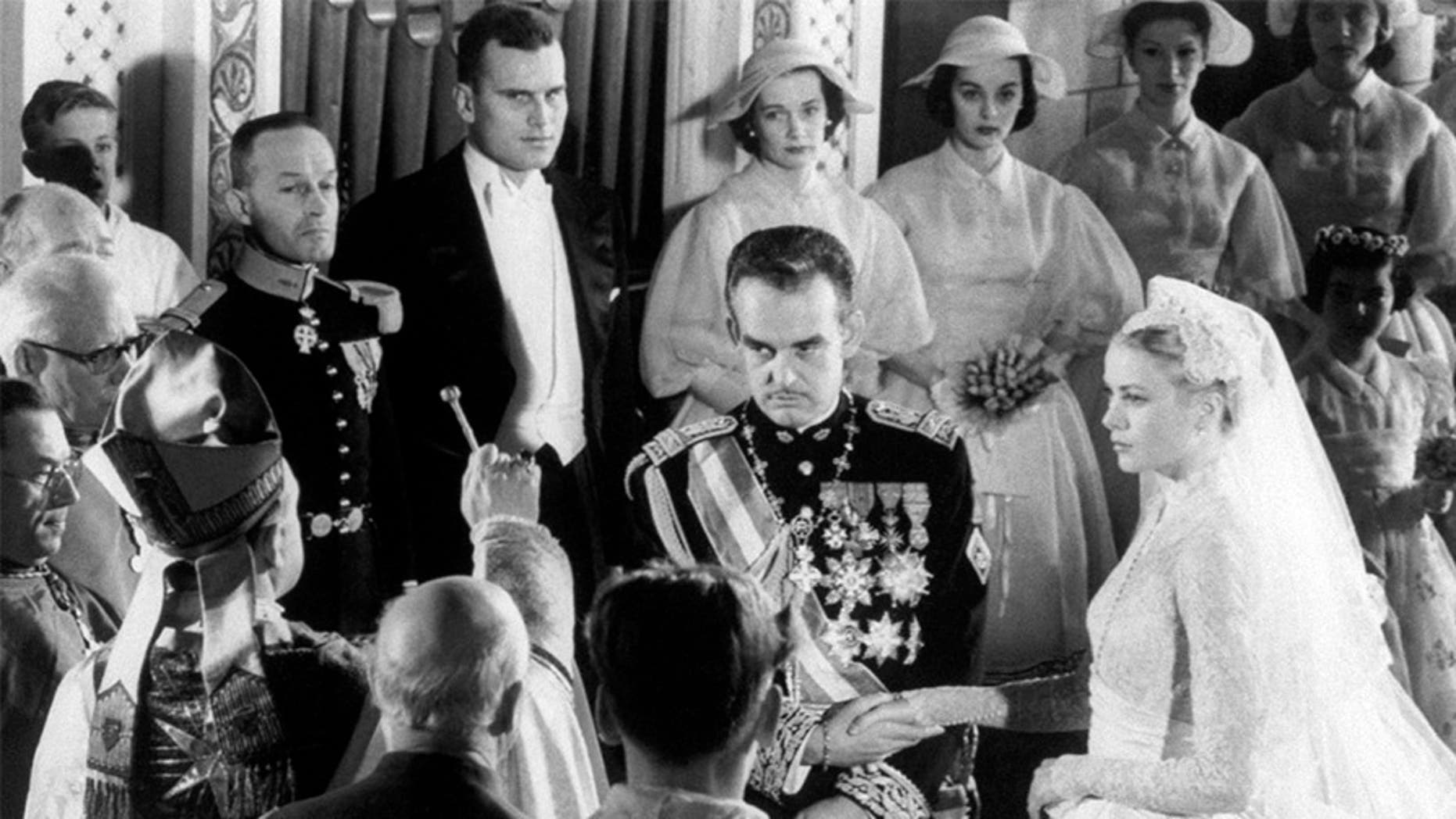Prince Rainier of Monaco and actress Grace Kelly join hands as Bishop of Monte Carlo Mgr. Gilles Barthe gives them nuptial benediction, during their wedding ceremony at Saint Nicholas Cathedral.