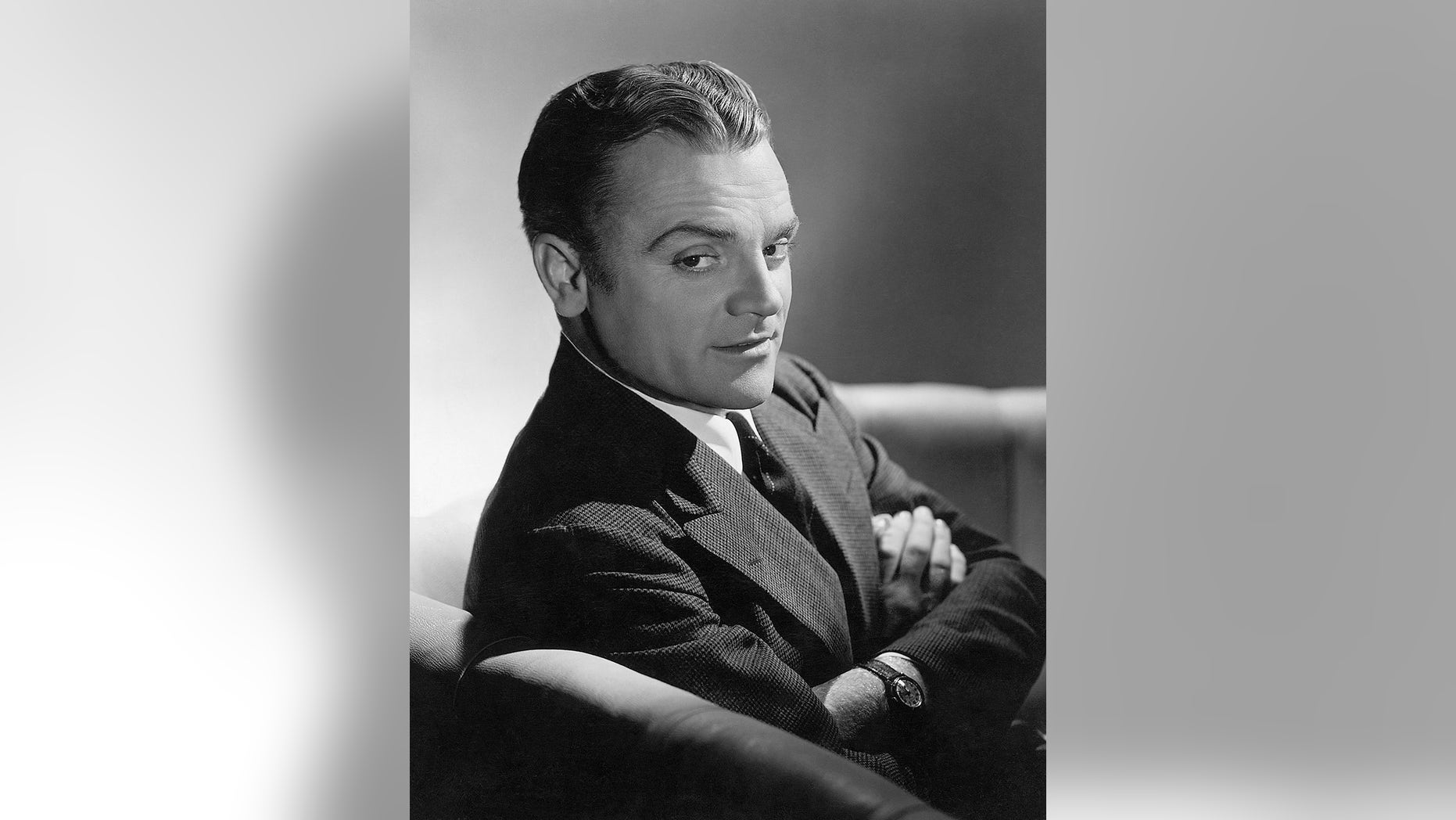 Close-up of actor James Cagney sitting on a sofa with his arms folded across his chest.