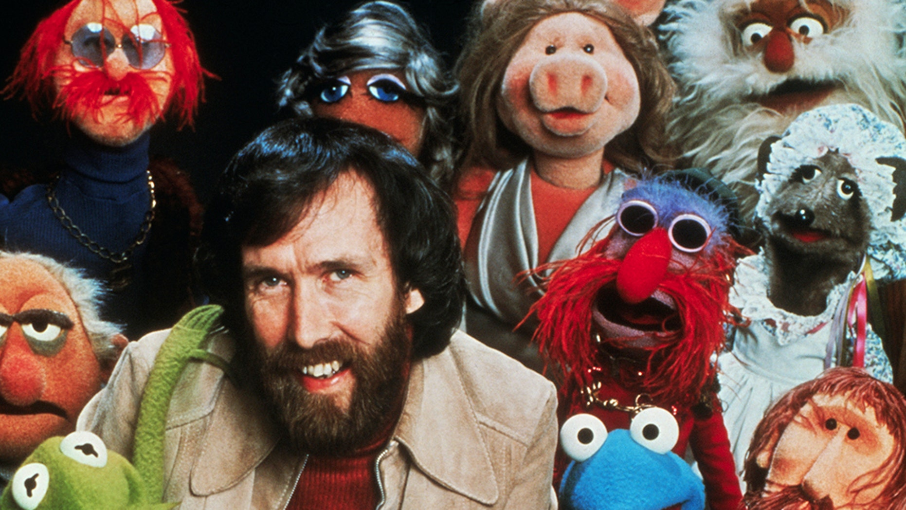 "Jim Henson, American puppeteer and creator of ""The Muppets,"" poses with his creations."