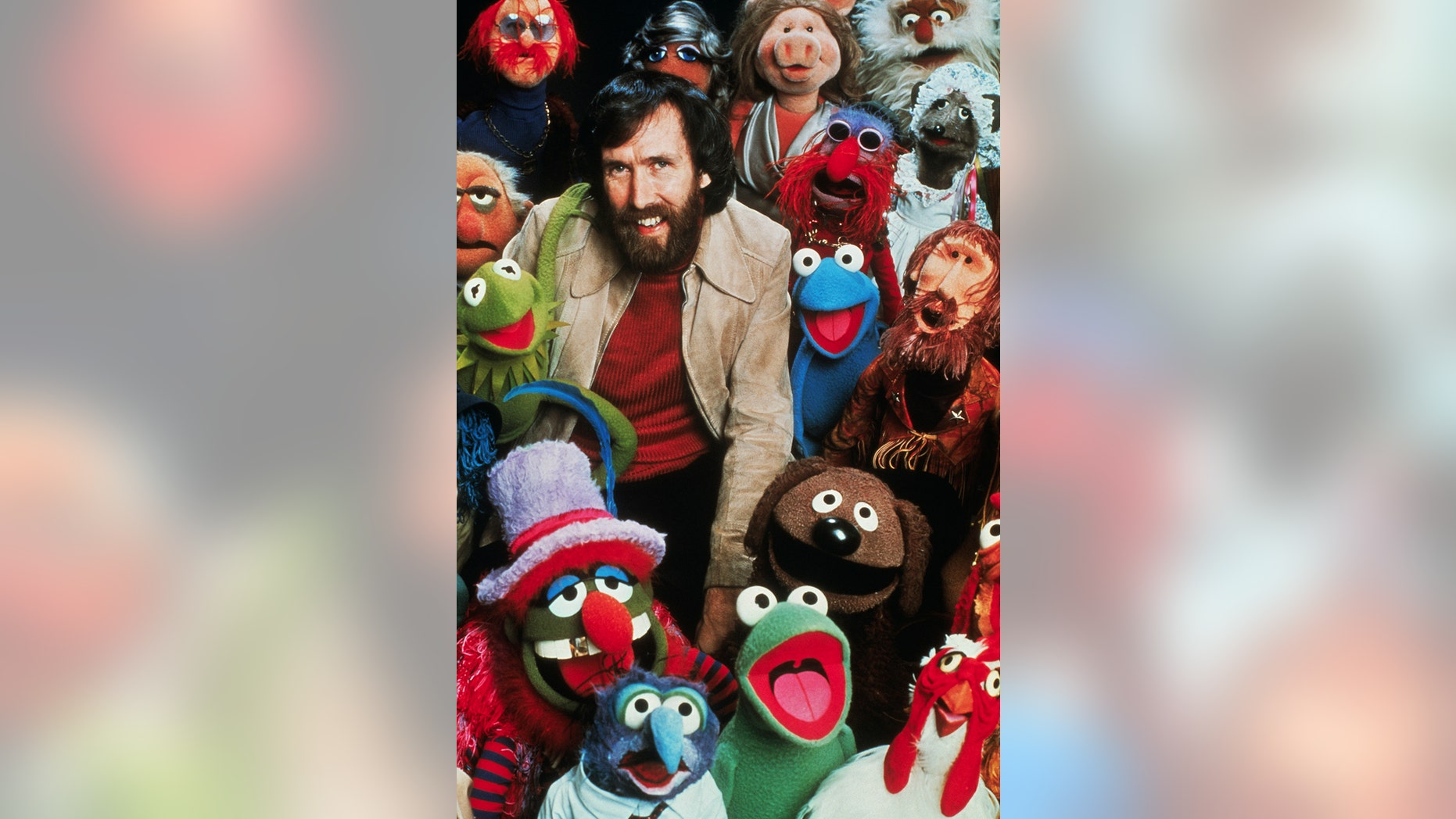 """Jim Henson, American puppeteer and creator of """"The Muppets,"""" poses with his creations."""